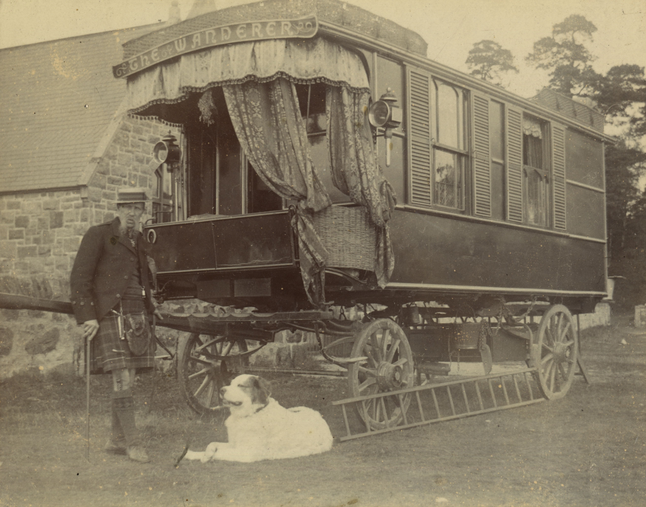 Gentleman and a dog standing by a caravan
