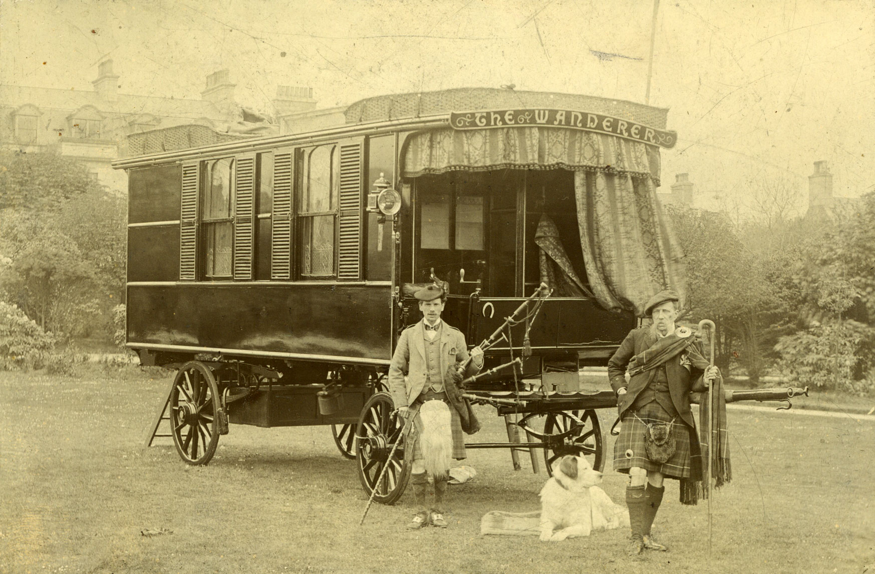 Two men in traditional Scottish dress and a dog standing in front of a caravan