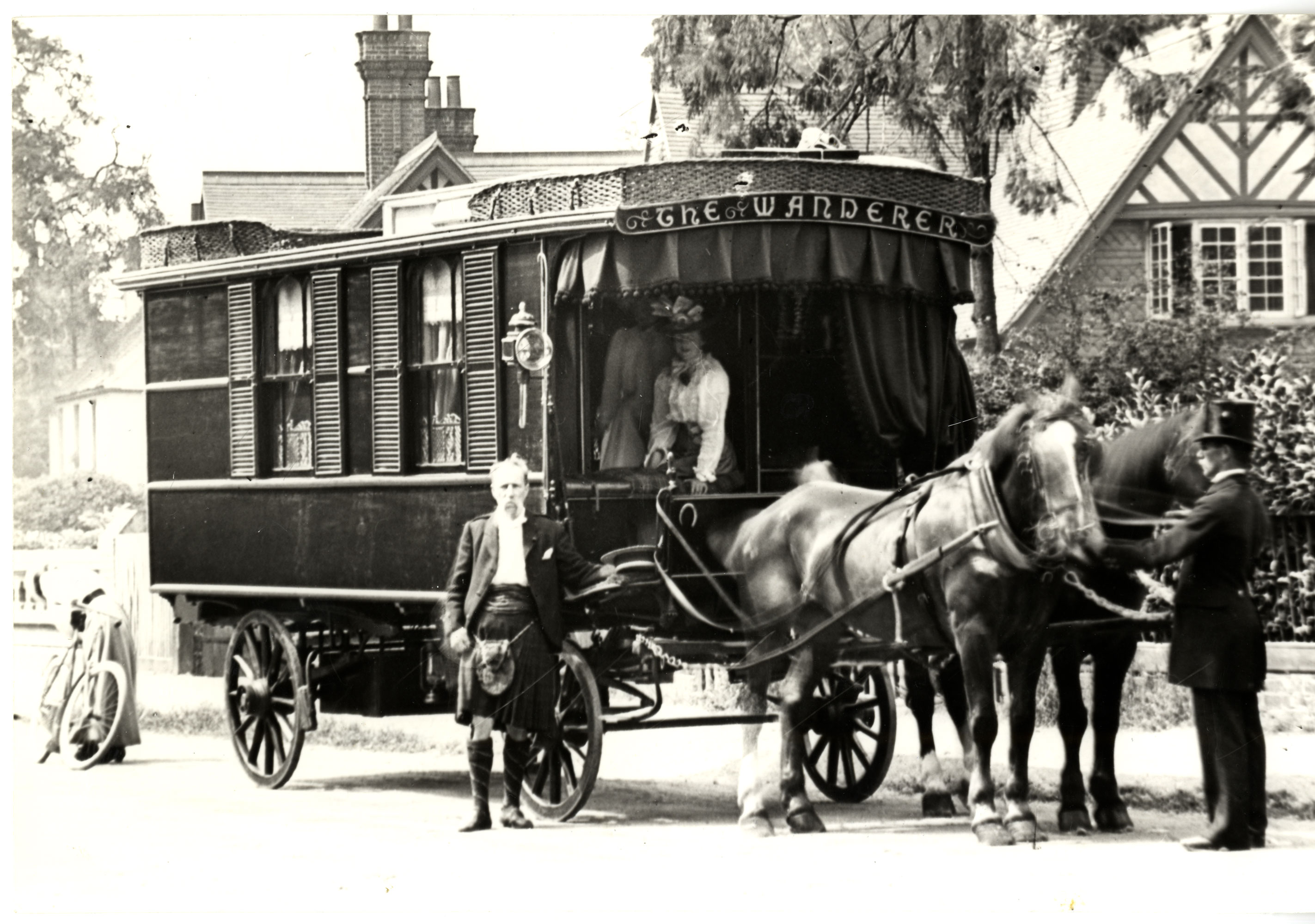 A caravan with two horses at the front with a footman