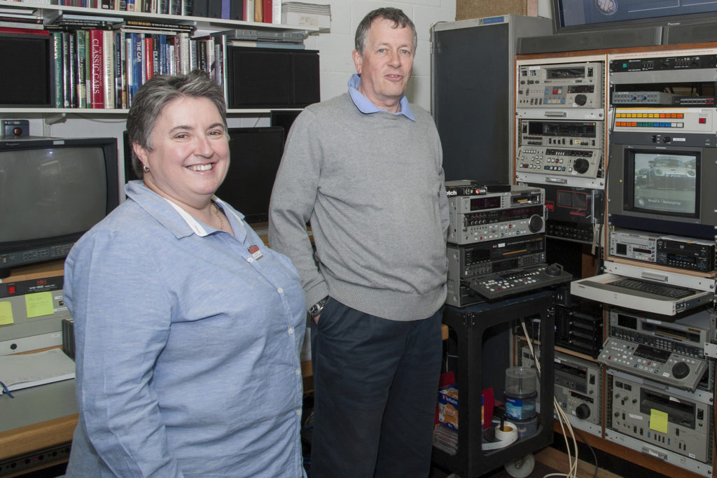 A man and a woman standing near some film equipment