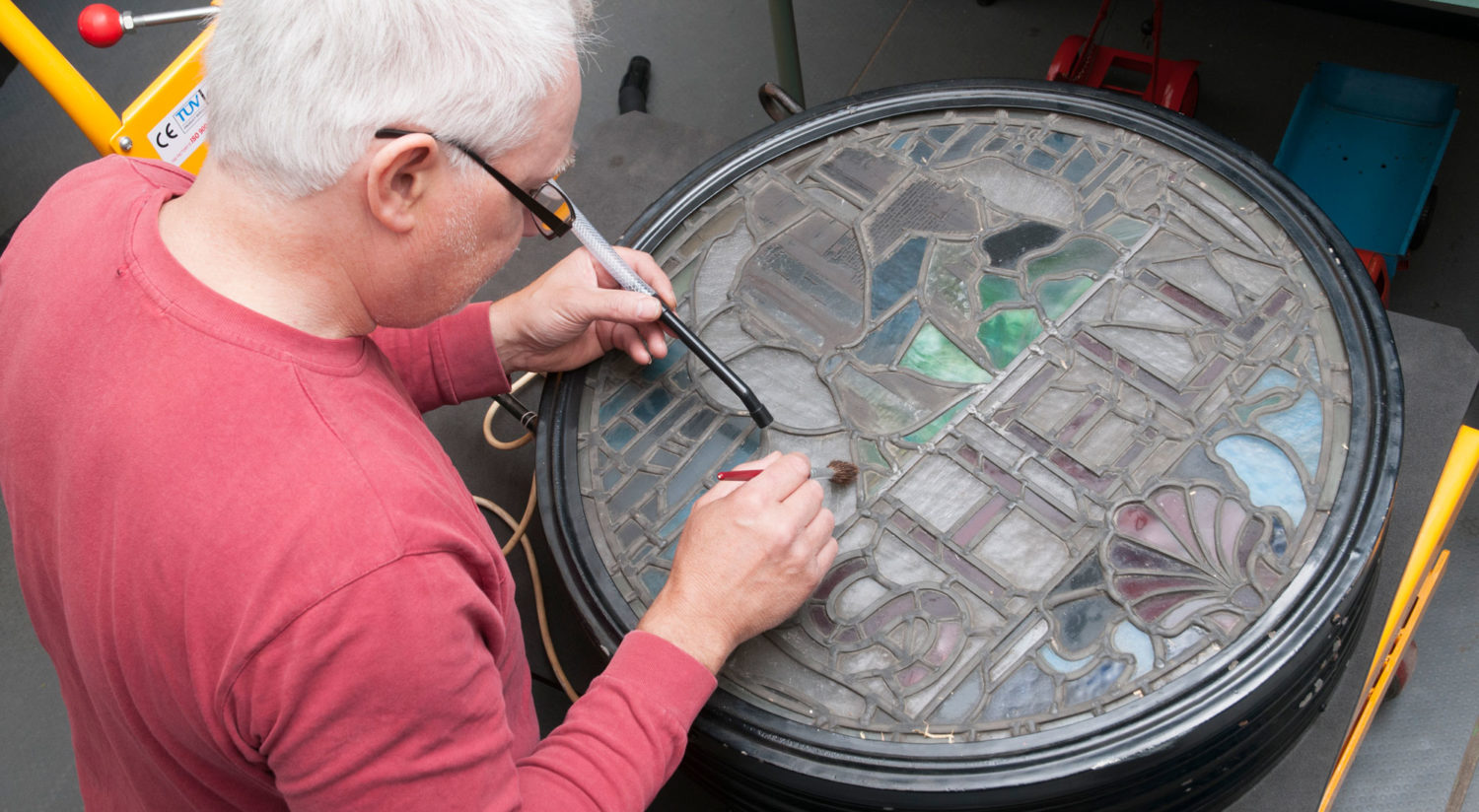 A man cleaning a stained-glass Shell petrol globe