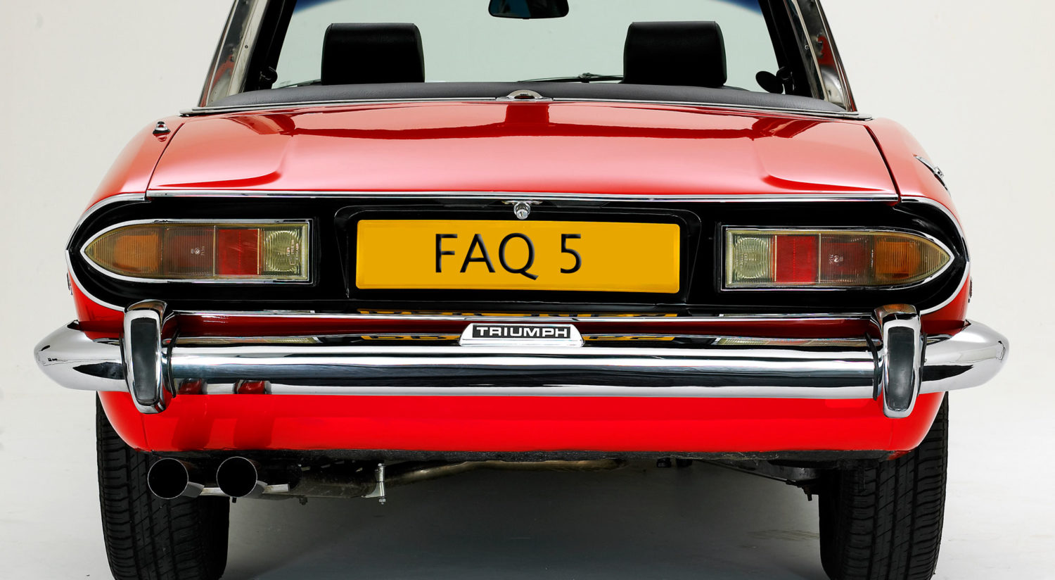 A red Triumph car with the number plate FAQ 5