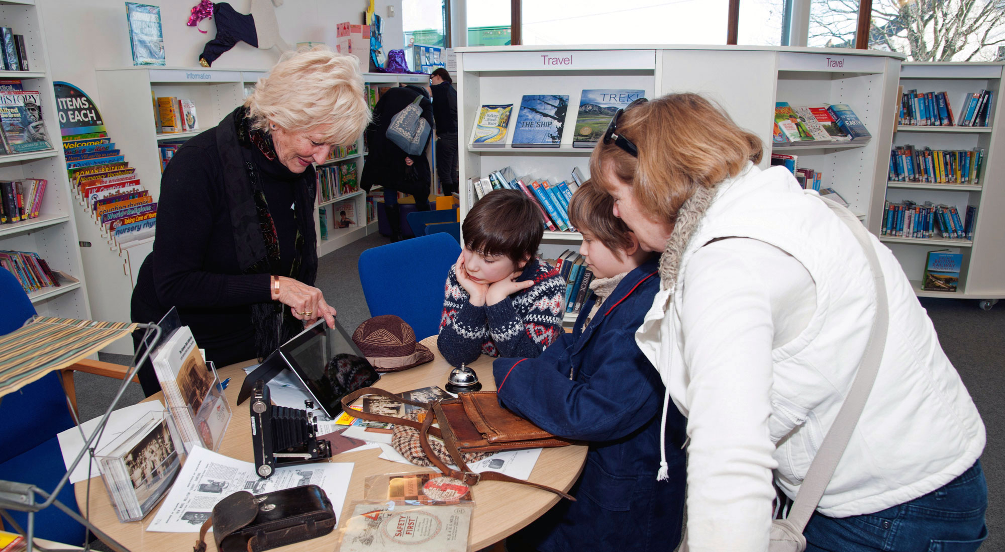 Lady showing museum objects to a family at Lymington Library