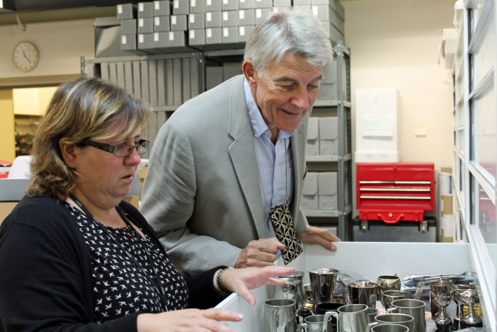Two people looking at a drawer of motoring silverware including cups and tankards
