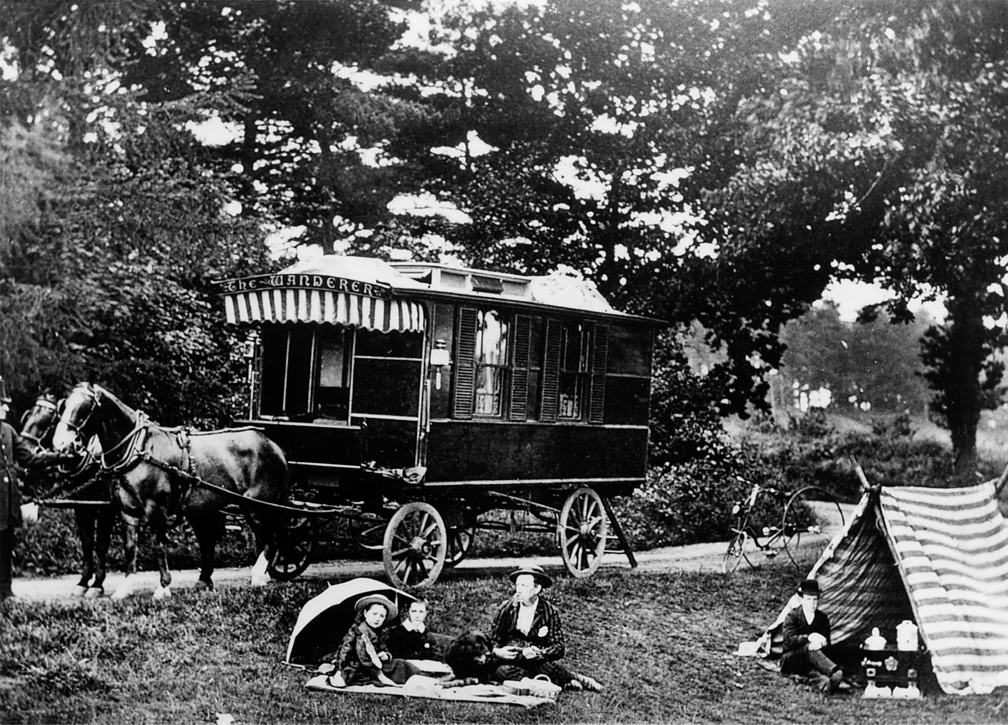 Caravan in the background with a group seated on a blanket in the foreground