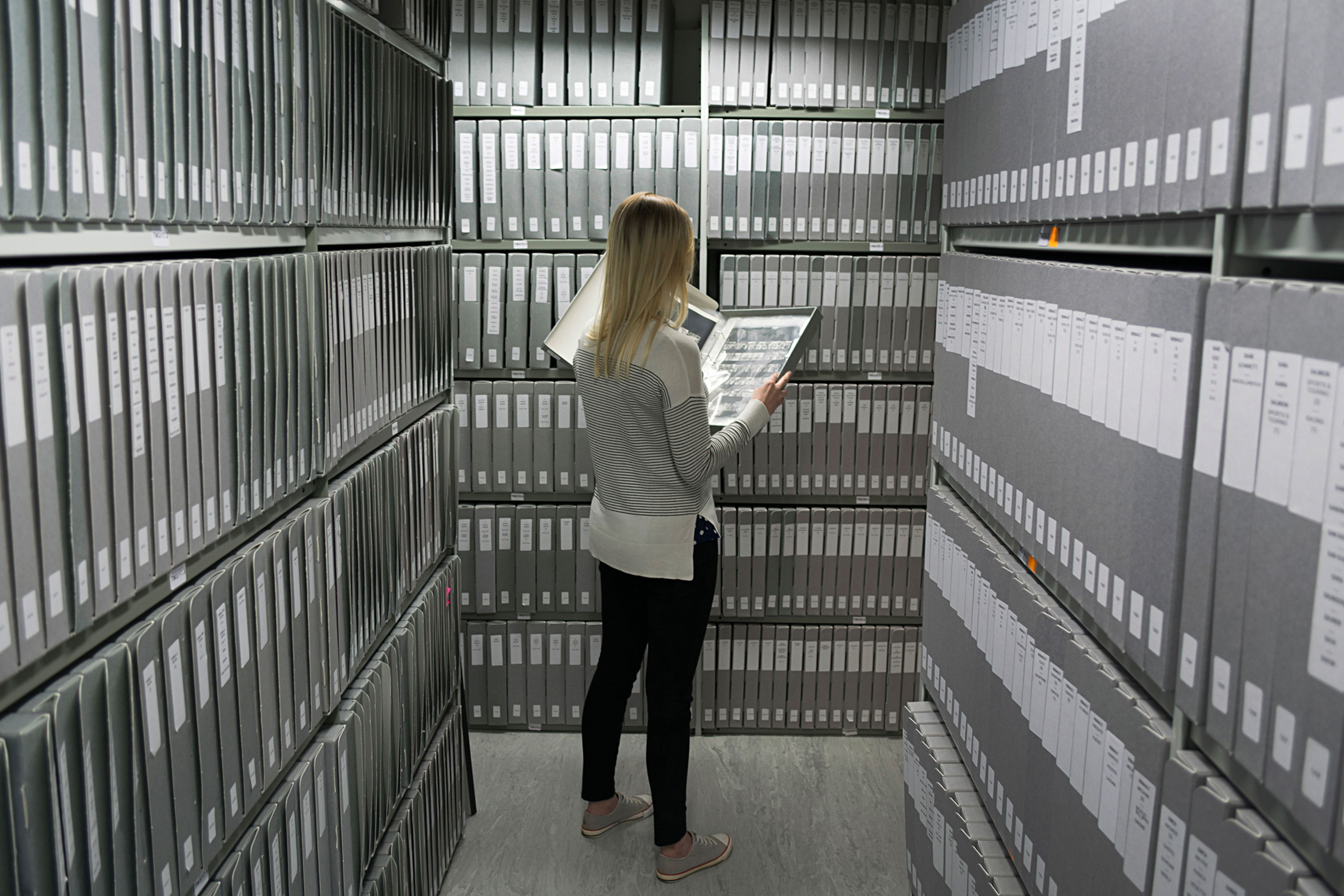 A woman looking at a photograph surrounded by many boxes on shelves