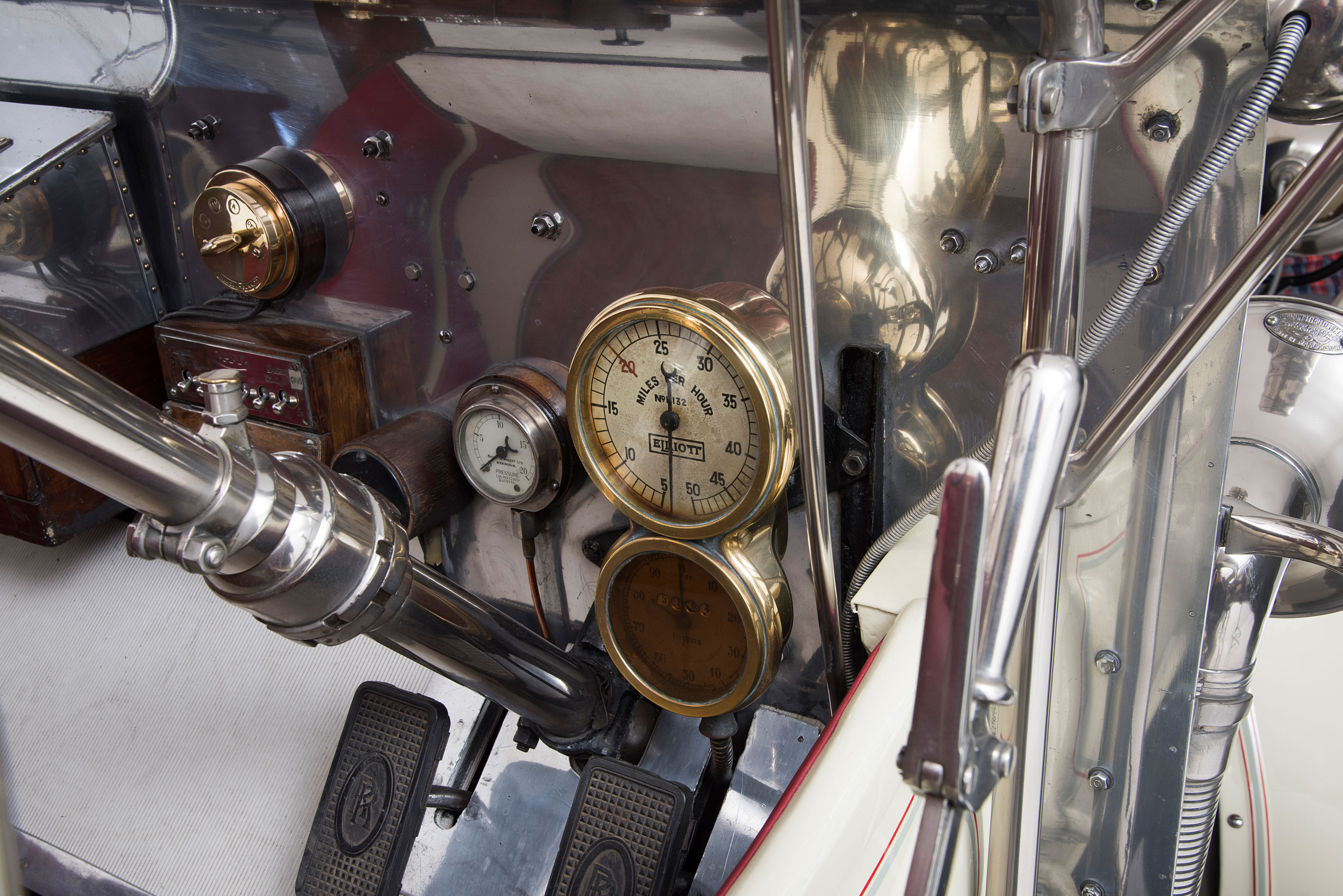 A close-up of a 1909 Rolls Royce showing the speedometer, pressure gauge and other parts