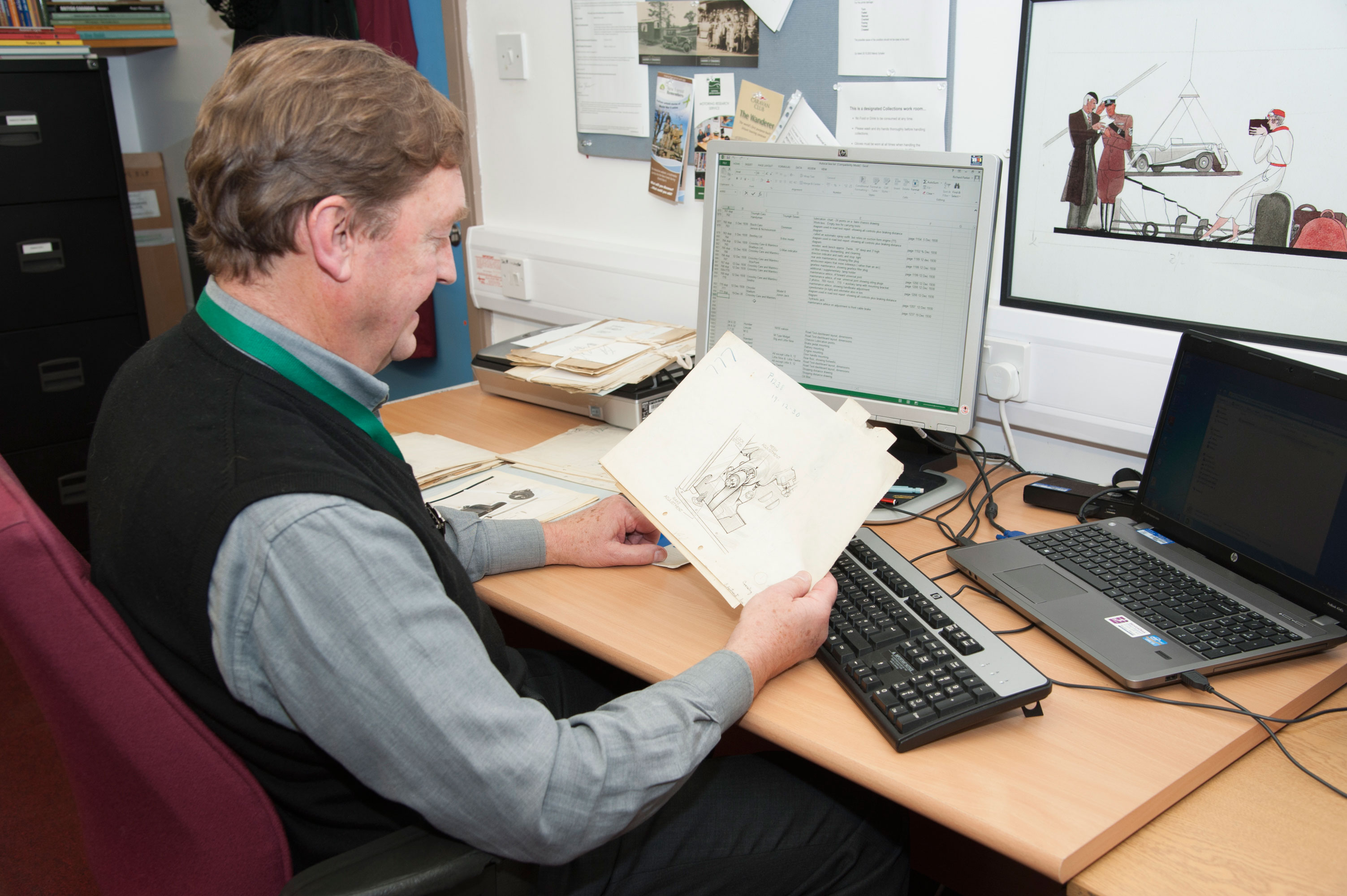 A volunteer inspecting a historic document from the National Motor Museum Trusts archives