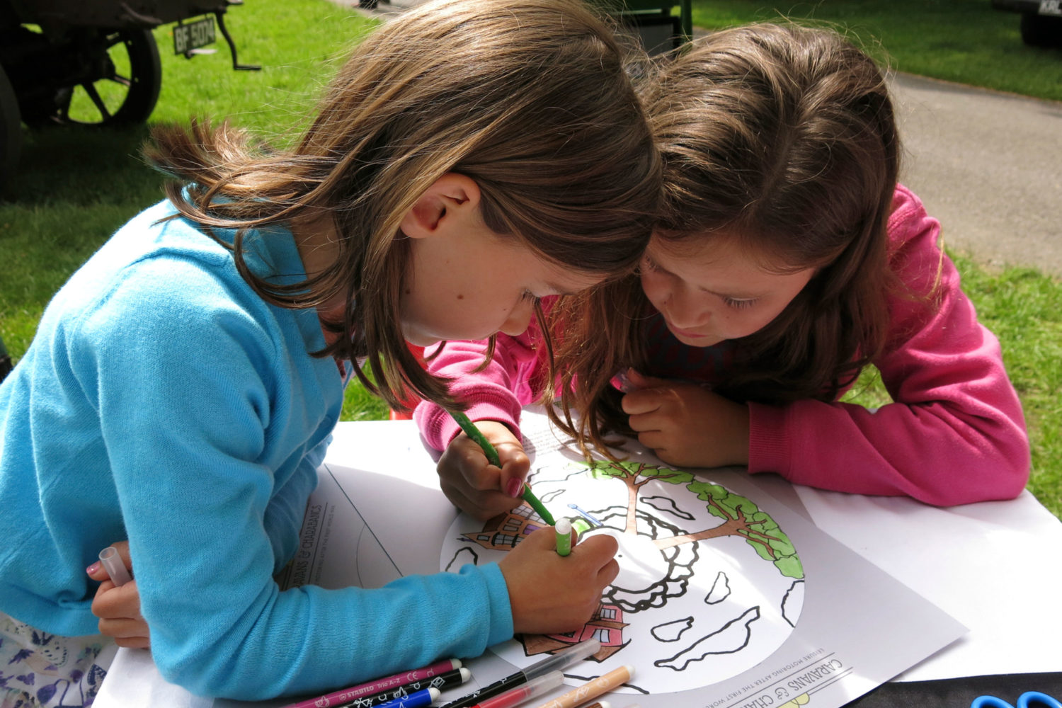 Two girls colouring in a picture of a charabanc outside at Beaulieu