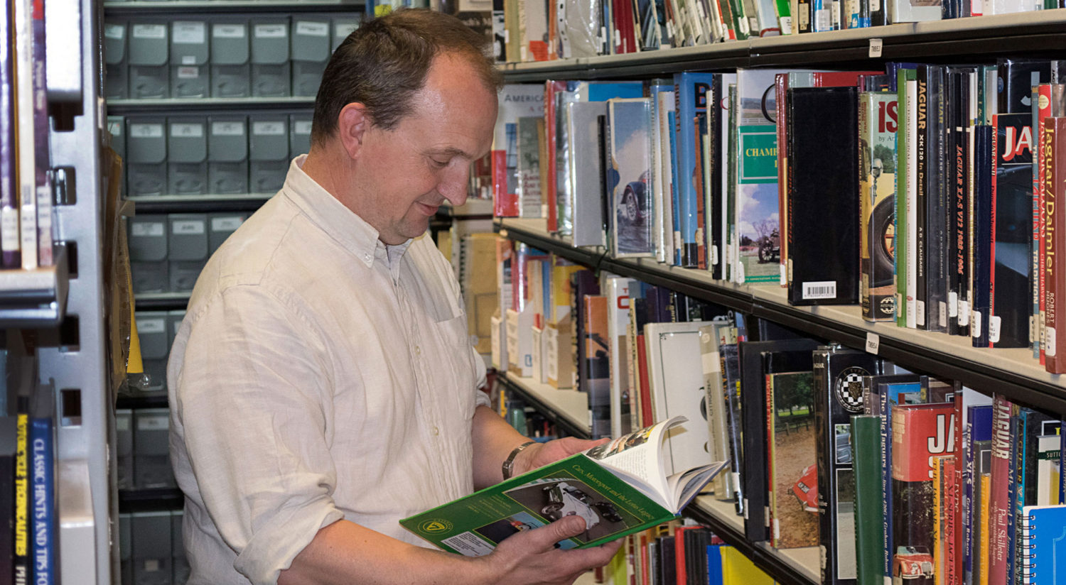 A man reading a book in the National Motor Museum library