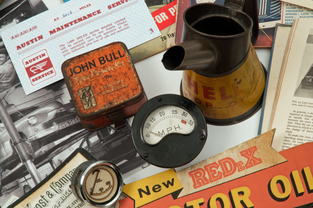 Historic motoring objects including a John Bull tin, a speedometer, a Shell oil funnel and an Austin service book