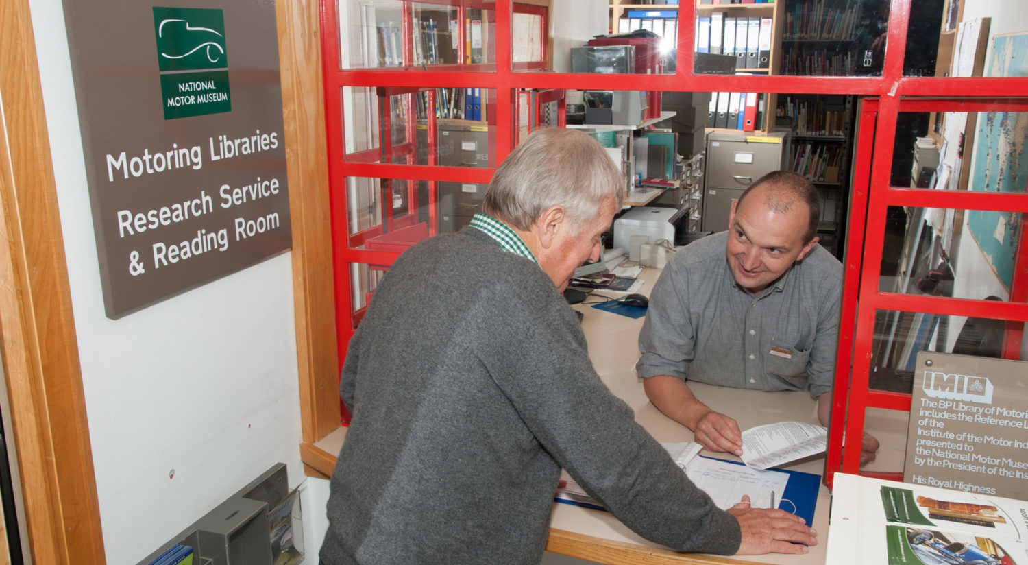 Two men at the enquiries window of the National Motor Museum Motoring Libraries Research Service & Reading Room