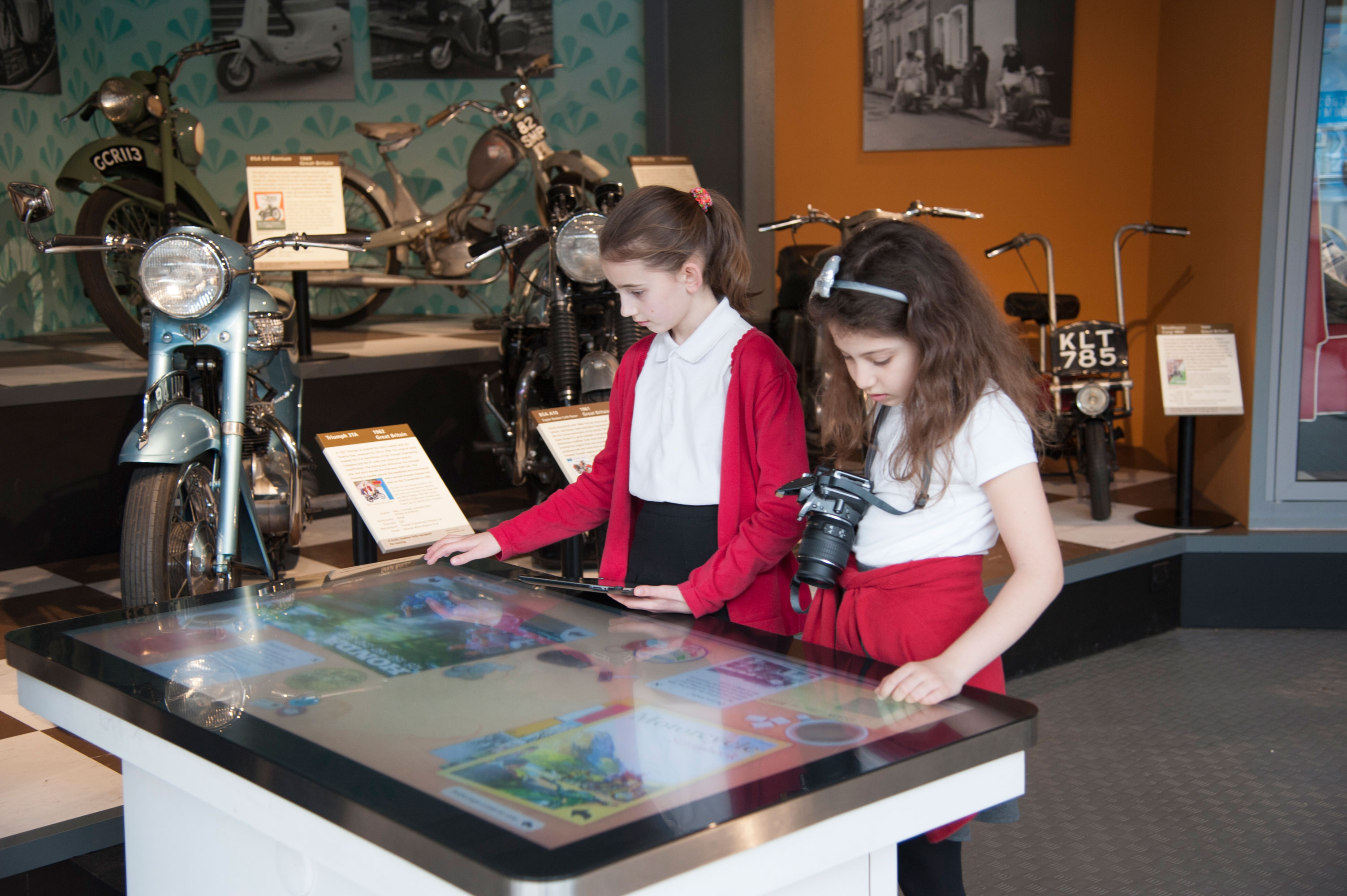 Two school children on a table top interactive at the National Motor Museum