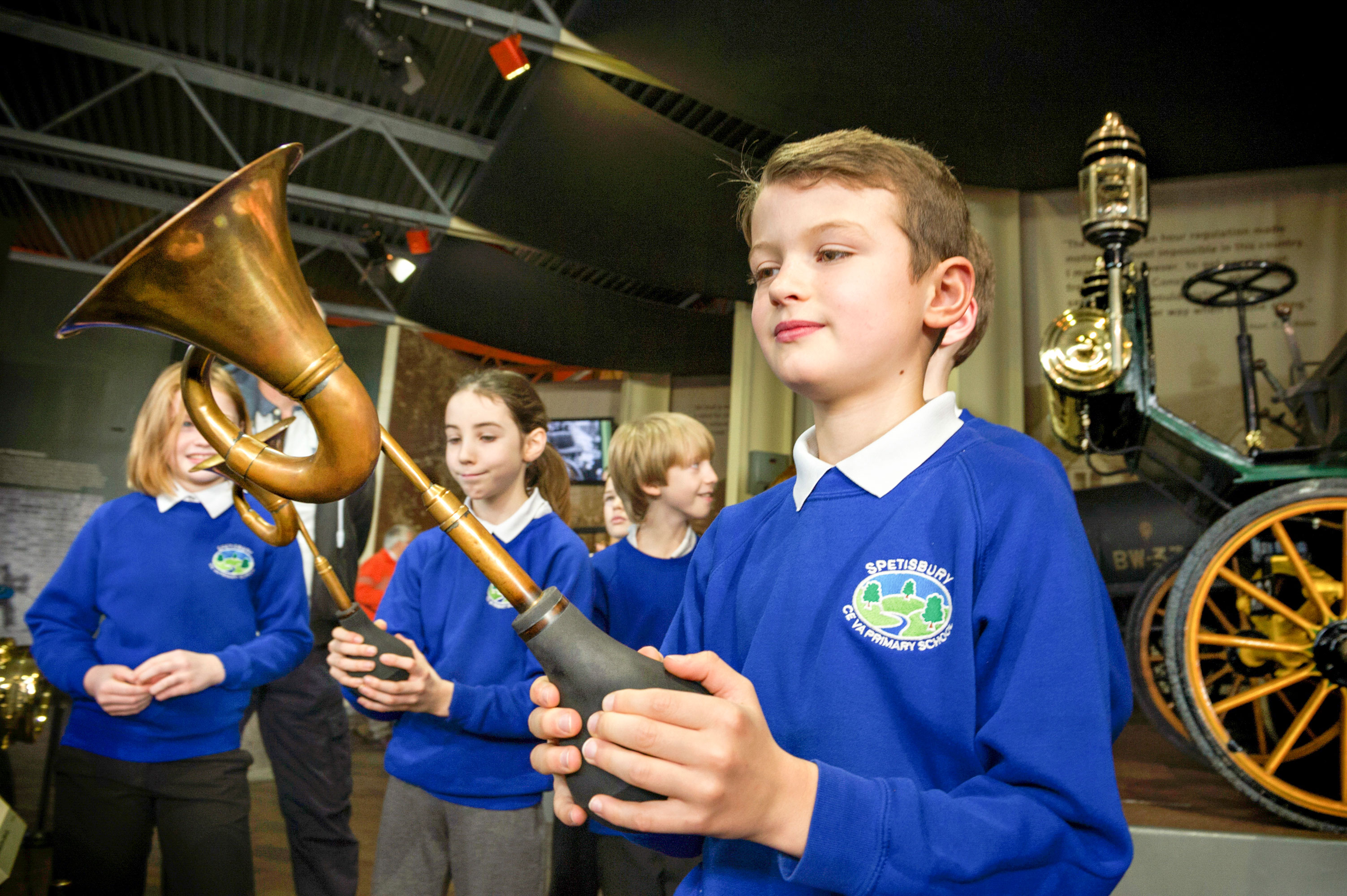 A schoolchild holding a historic car horn at the National Motor Museum
