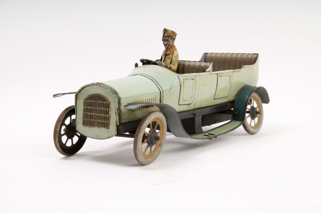 A green model vintage car with chauffeur