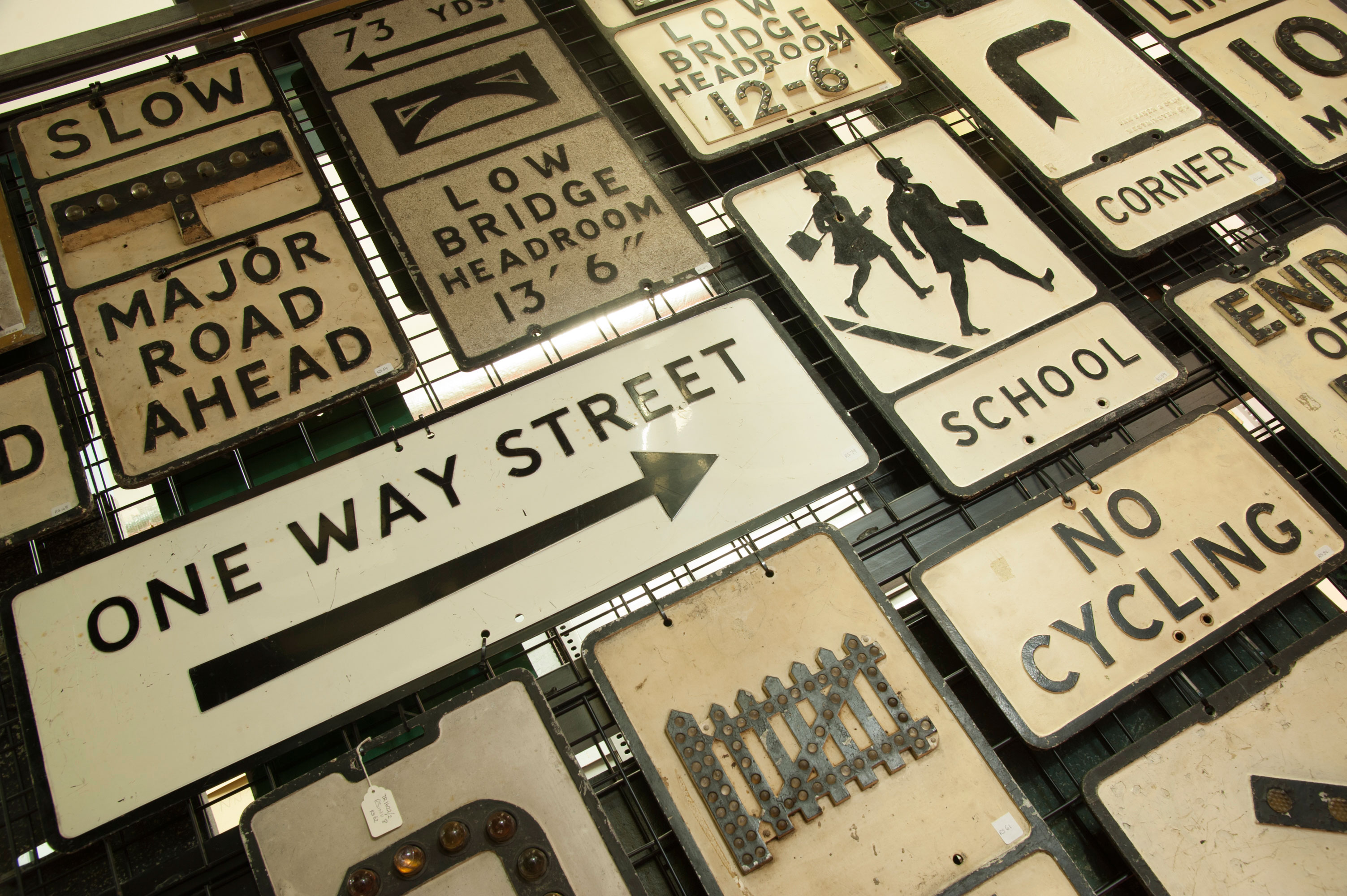 Old street signs for One Way Street, Major Road Ahead, School, No Cycling, Low Bridge