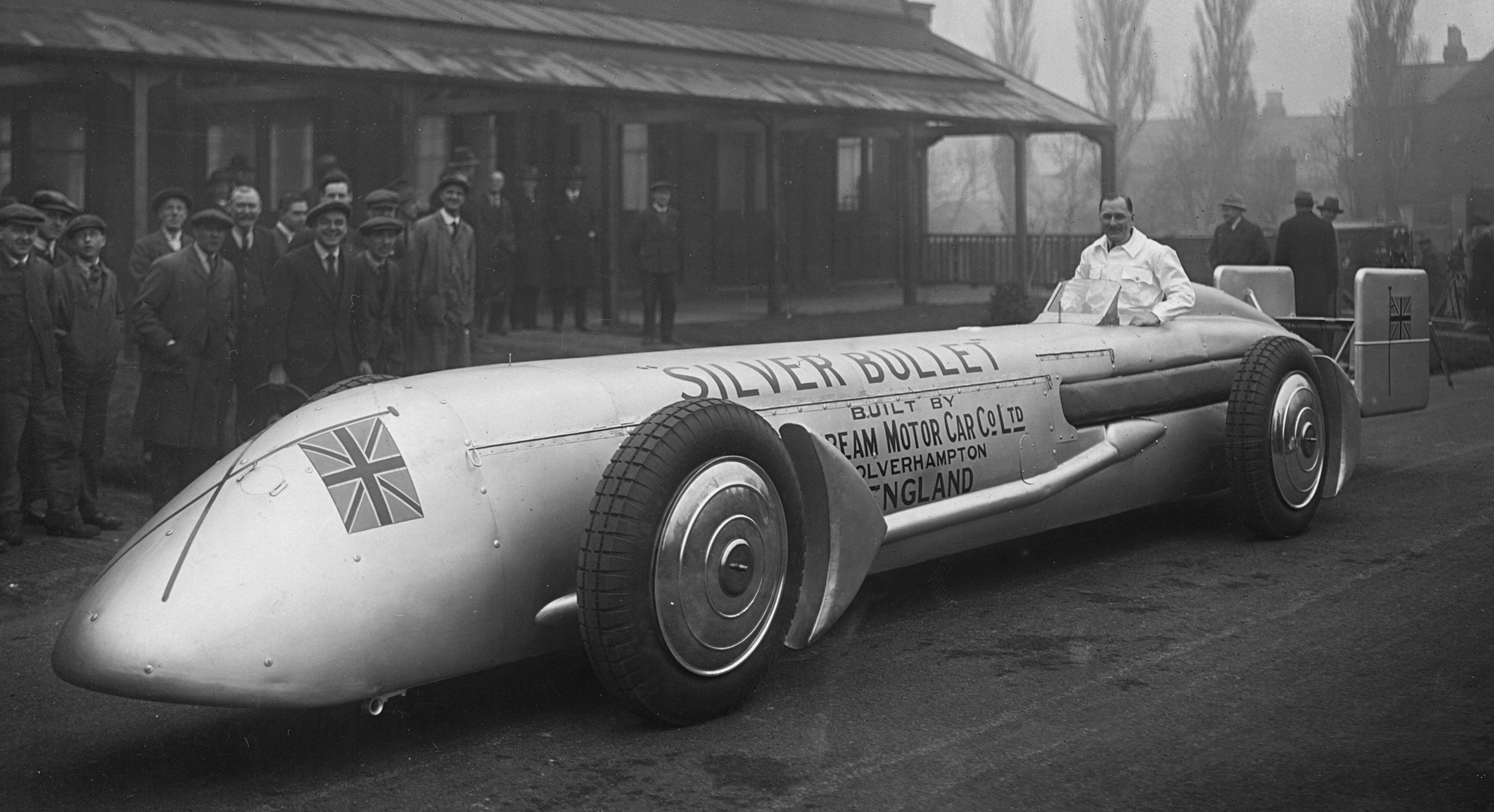 A historic black & white photograph of Kaye Don with the Silver Bullet at the factory in 1930