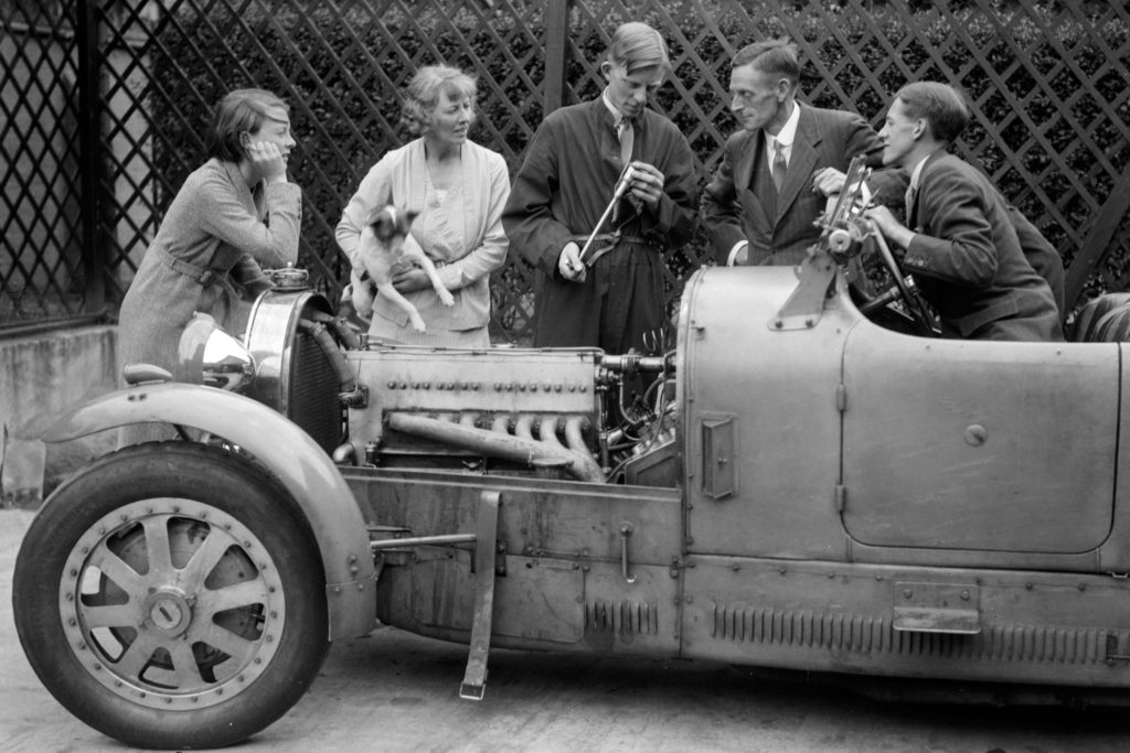 A historic black & white photograph of five people inspecting a Bugatti Type 43