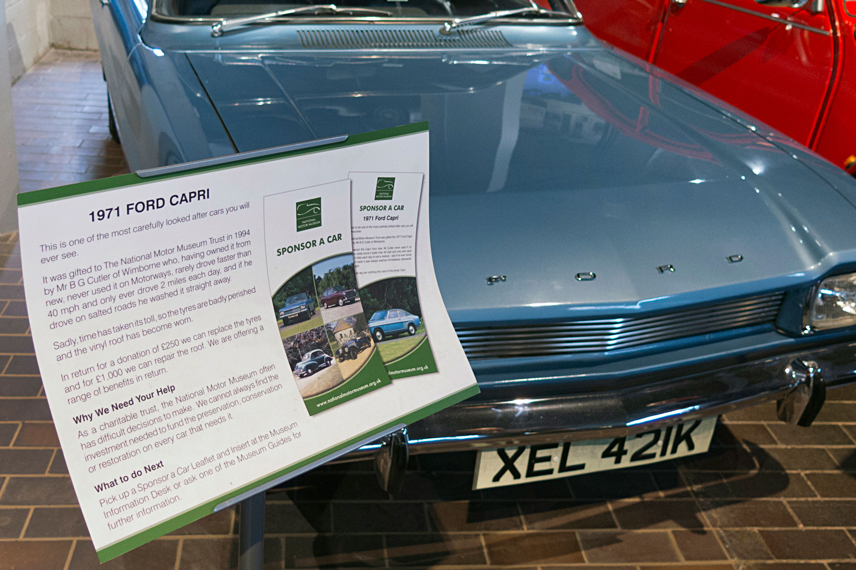 A sign next to a 1971 Ford Capri explaining the National Motor Museum's Sponsor a Vehicle scheme