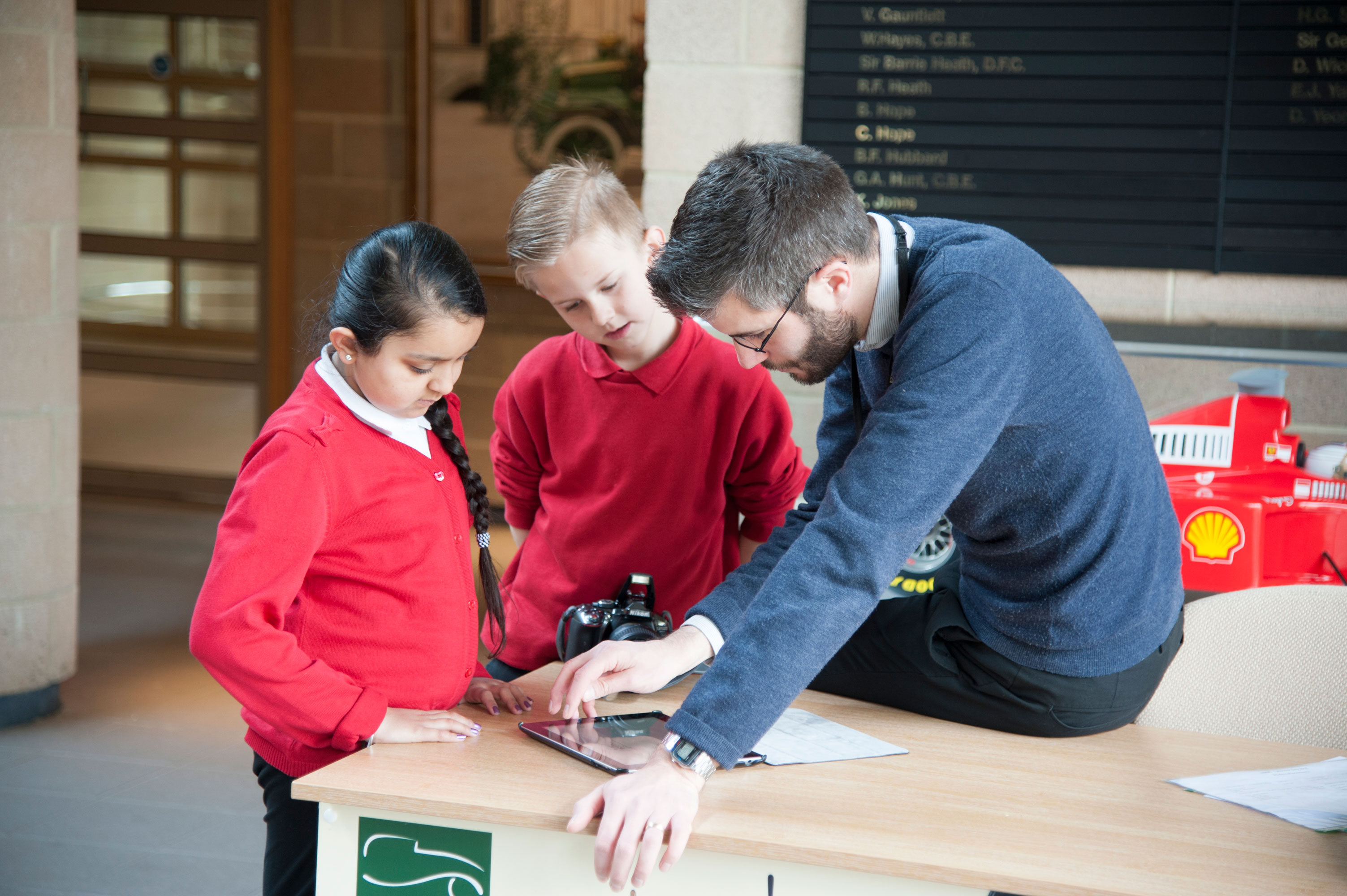 Two children with a member of National Motor Museum staff looking at an ipad