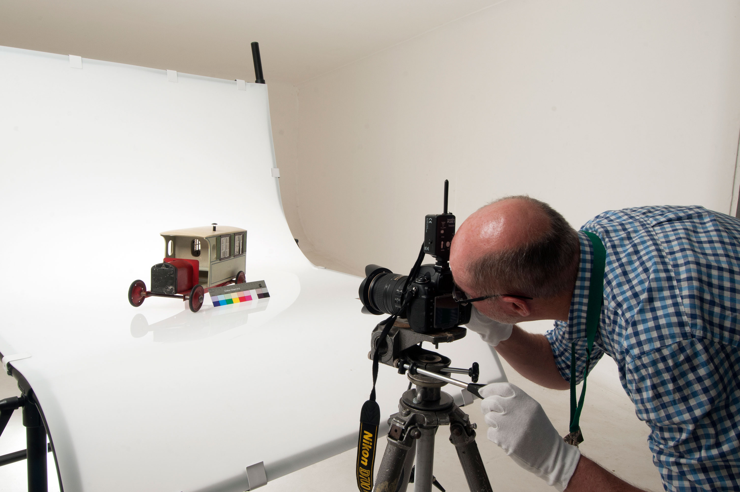 A man in a photographic studio taking a photograph of a historic toy car