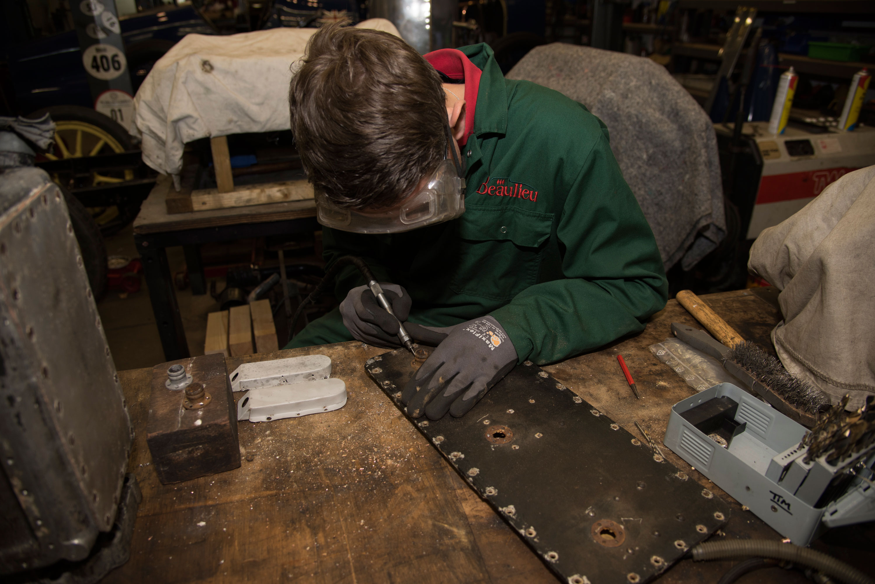 An engineer wearing Beaulieu overalls in a workshop repairing part of a historic vehicle