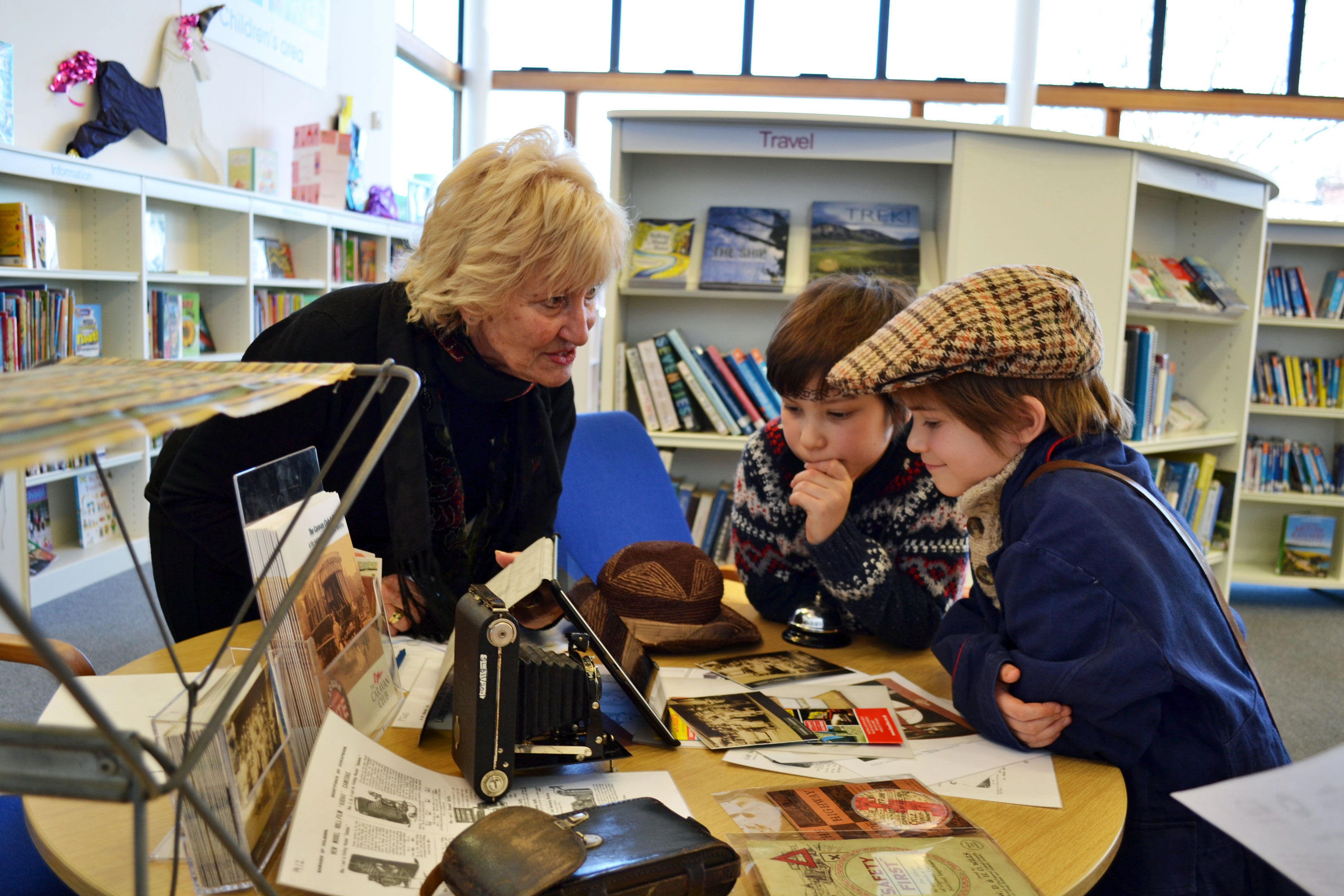 In a local library a woman shows two children some objects from the Caravan and Motorhome Club Collection