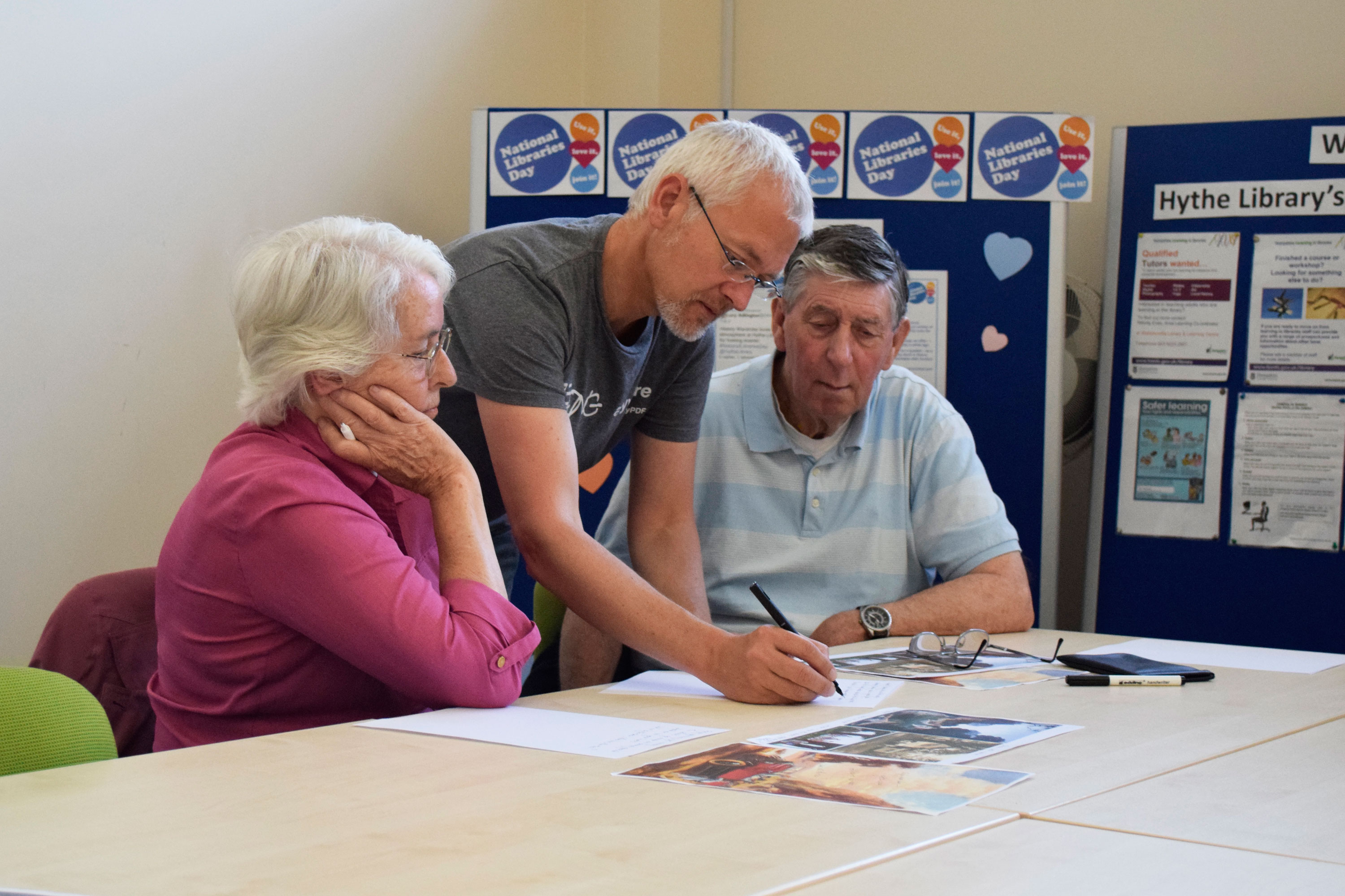 Man working with two people during a reminiscence session at Hythe Library