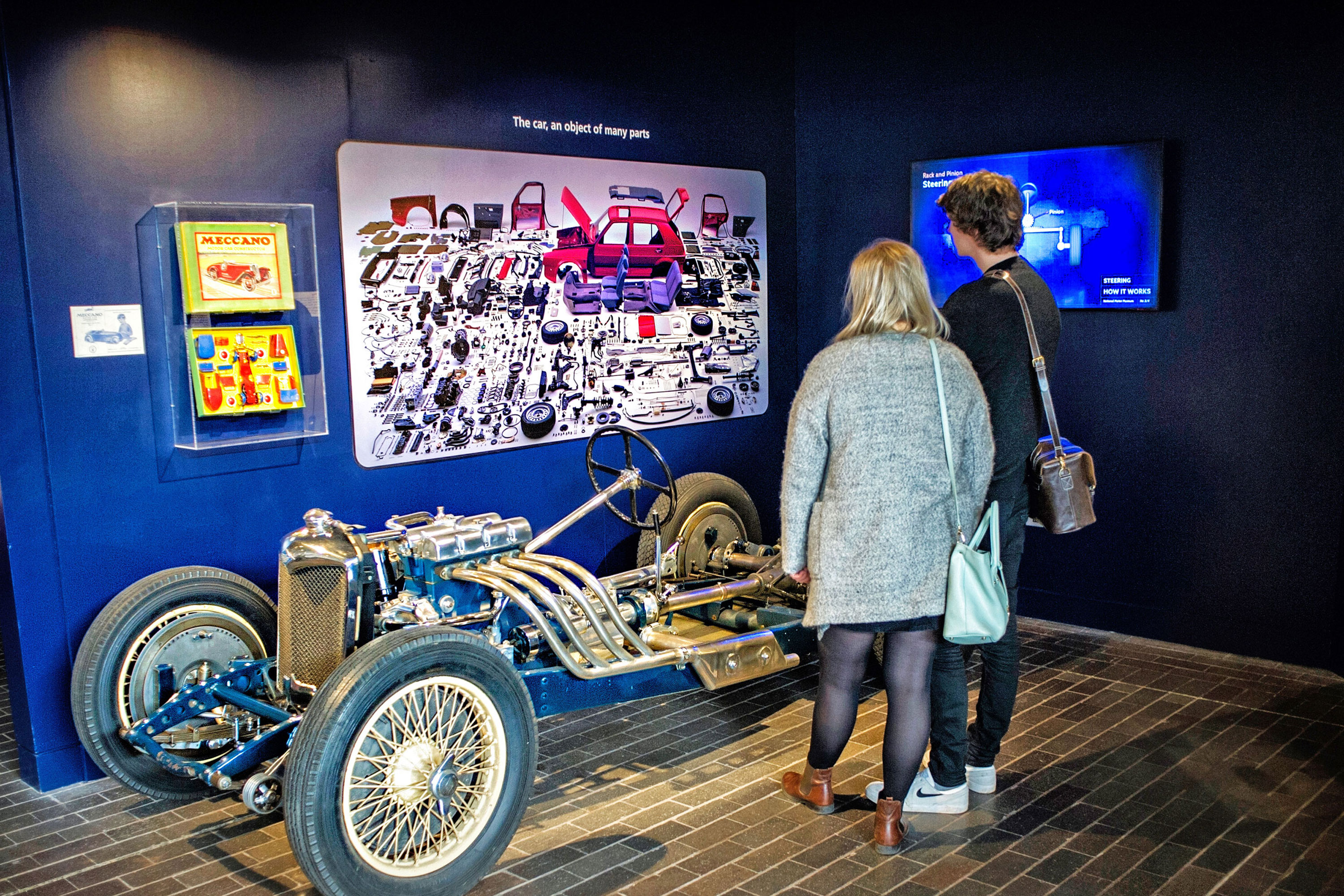 Two people looking at a car at the National Motor Museum