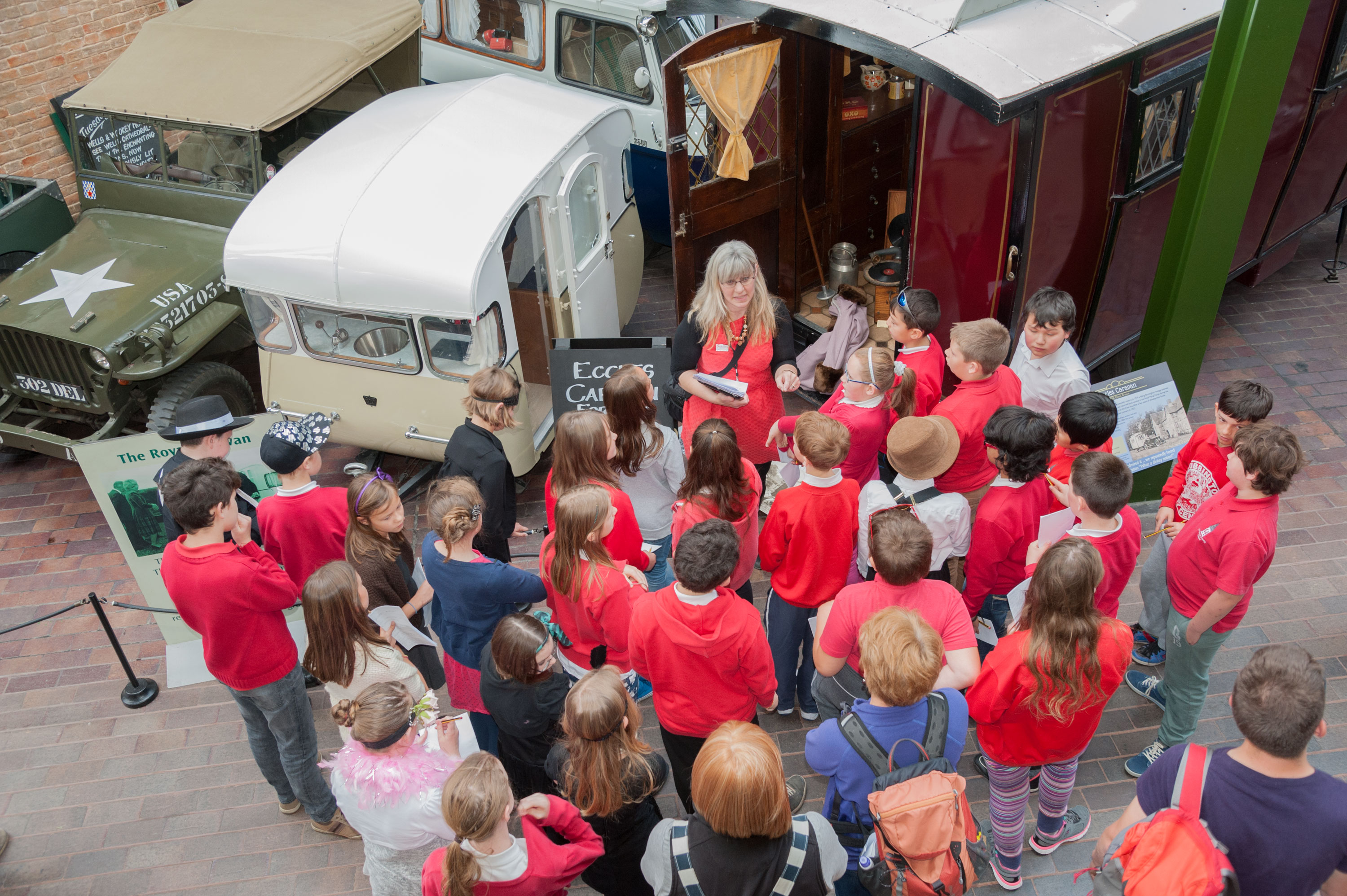 A group of schoolchildren stand next to the Eccles and Royal caravans in the National Motor Museum
