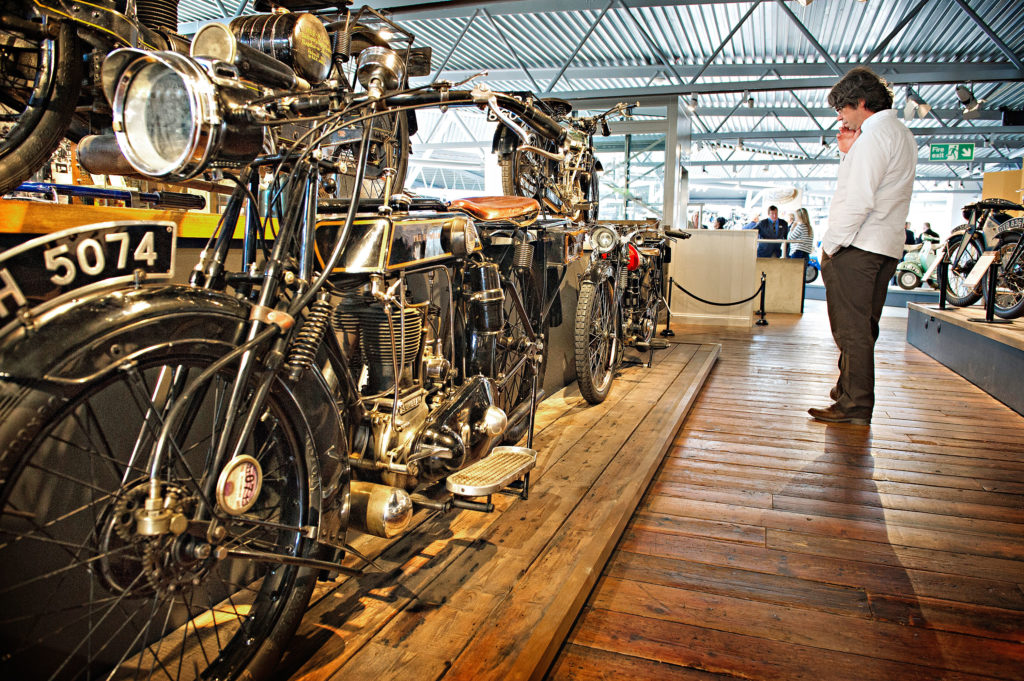 Man looking at vintage motorcycles at the National Motor Museum