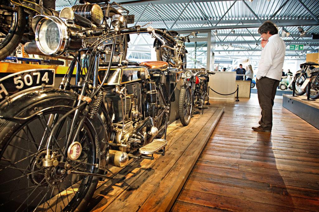 Man looking at vintage motorcycles at the National Motor Museum