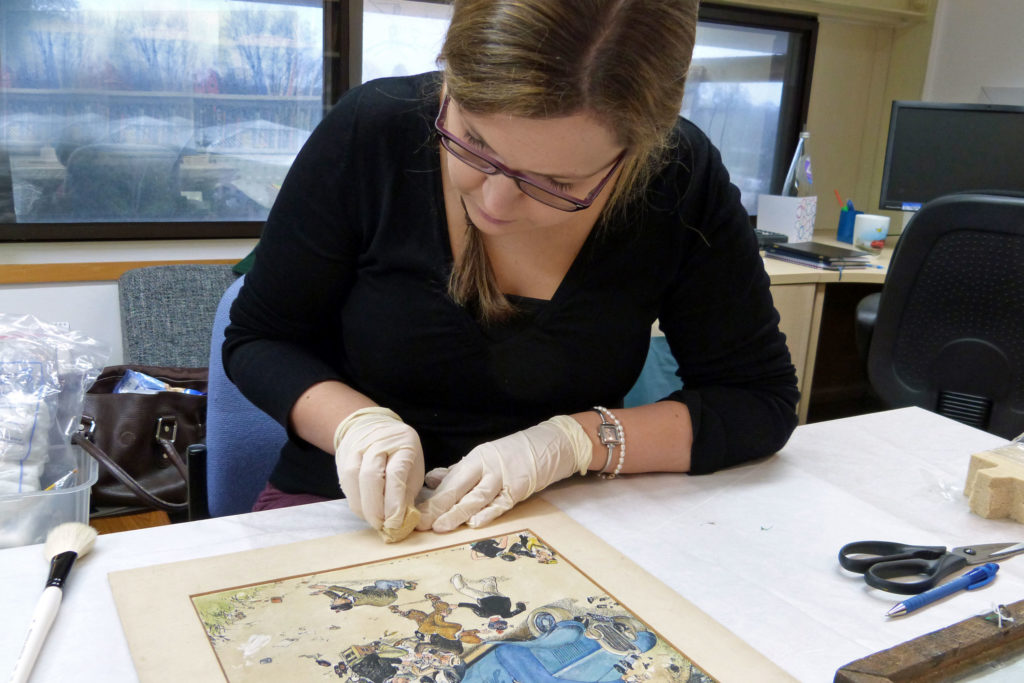 A museum curator carrying out the conservation of cartoon print