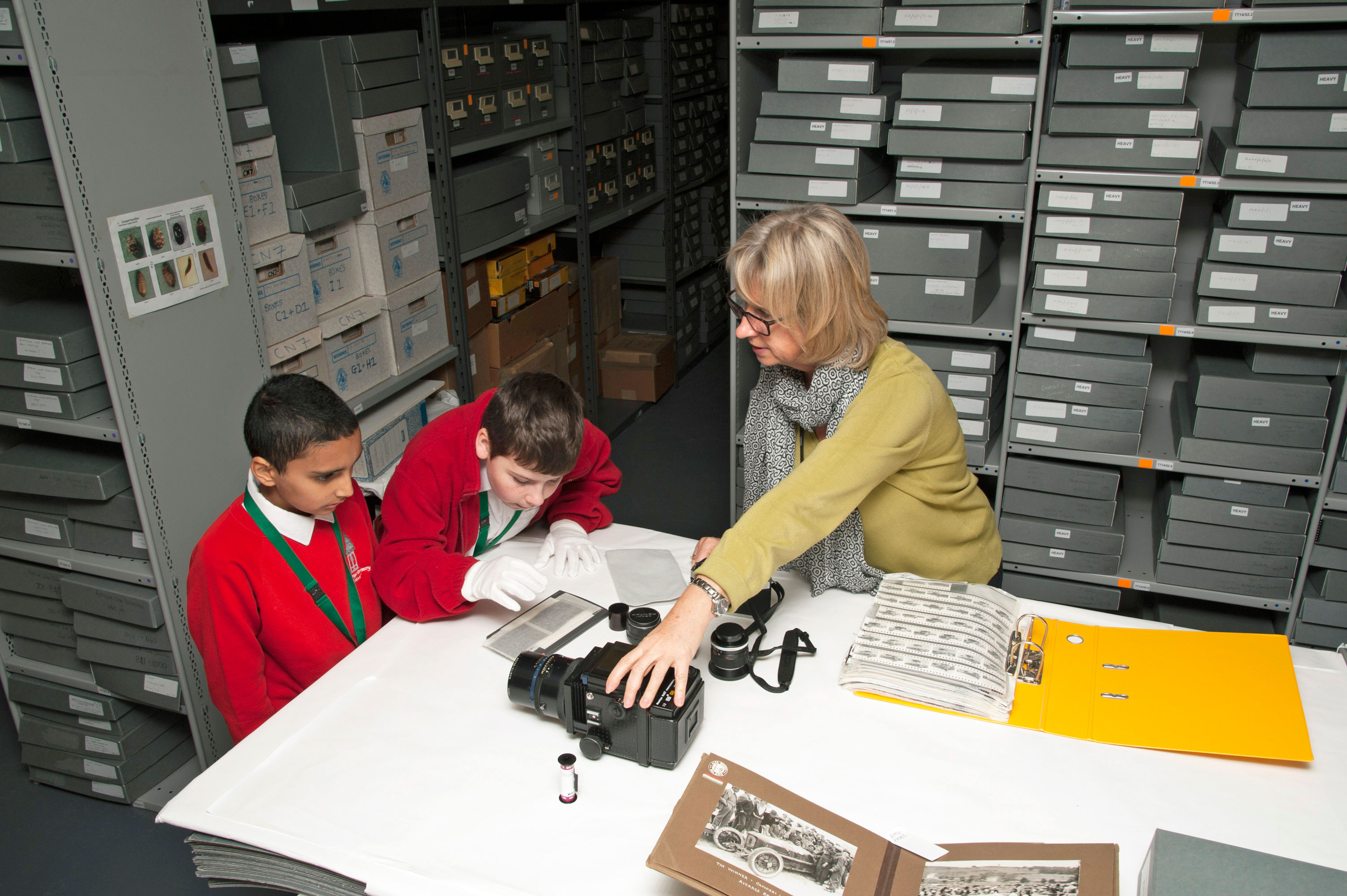 A museum curator showing two school children an old camera and some historic photgraphs