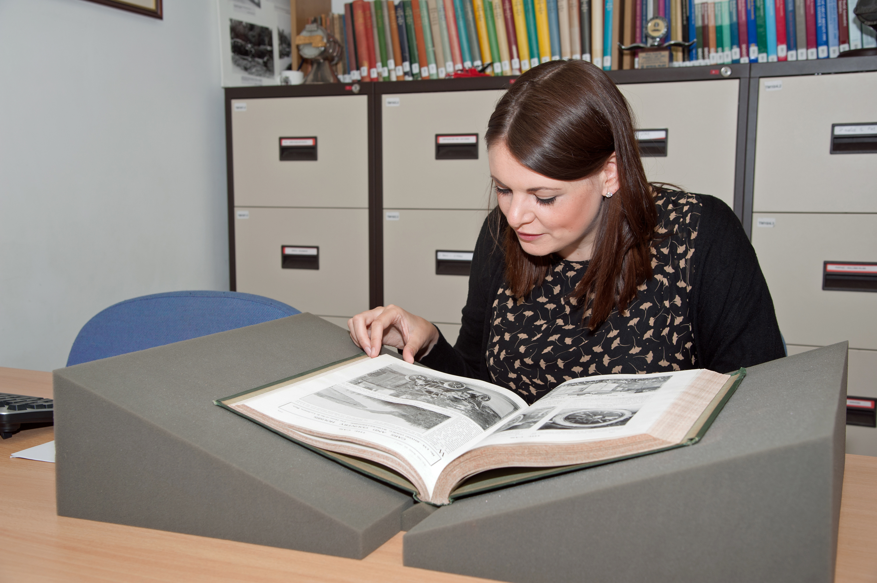 Woman reading a historic book in the Collections Centre Reading Room