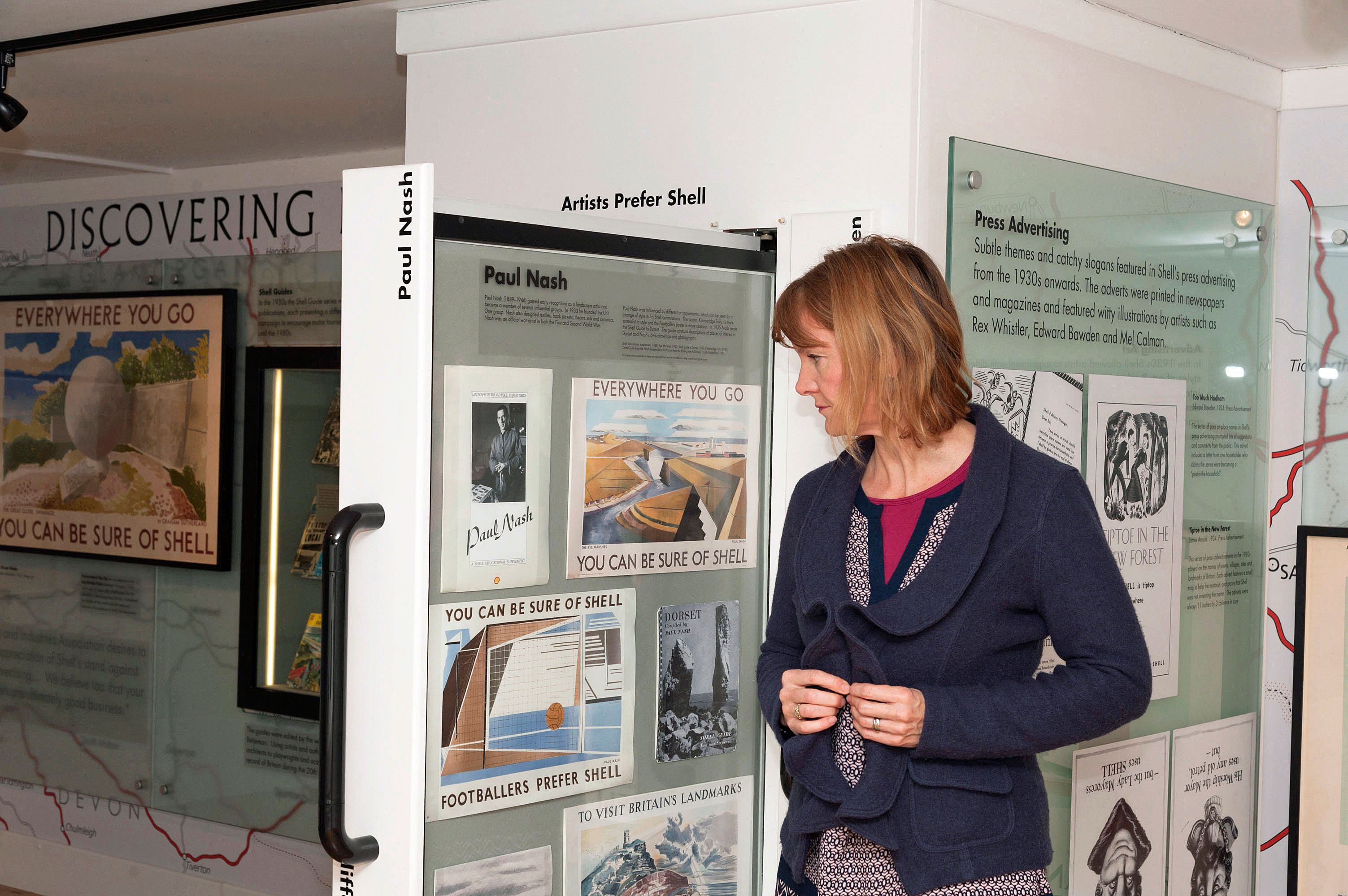 A woman looking at the Shell display booth at the National Motor Museum.