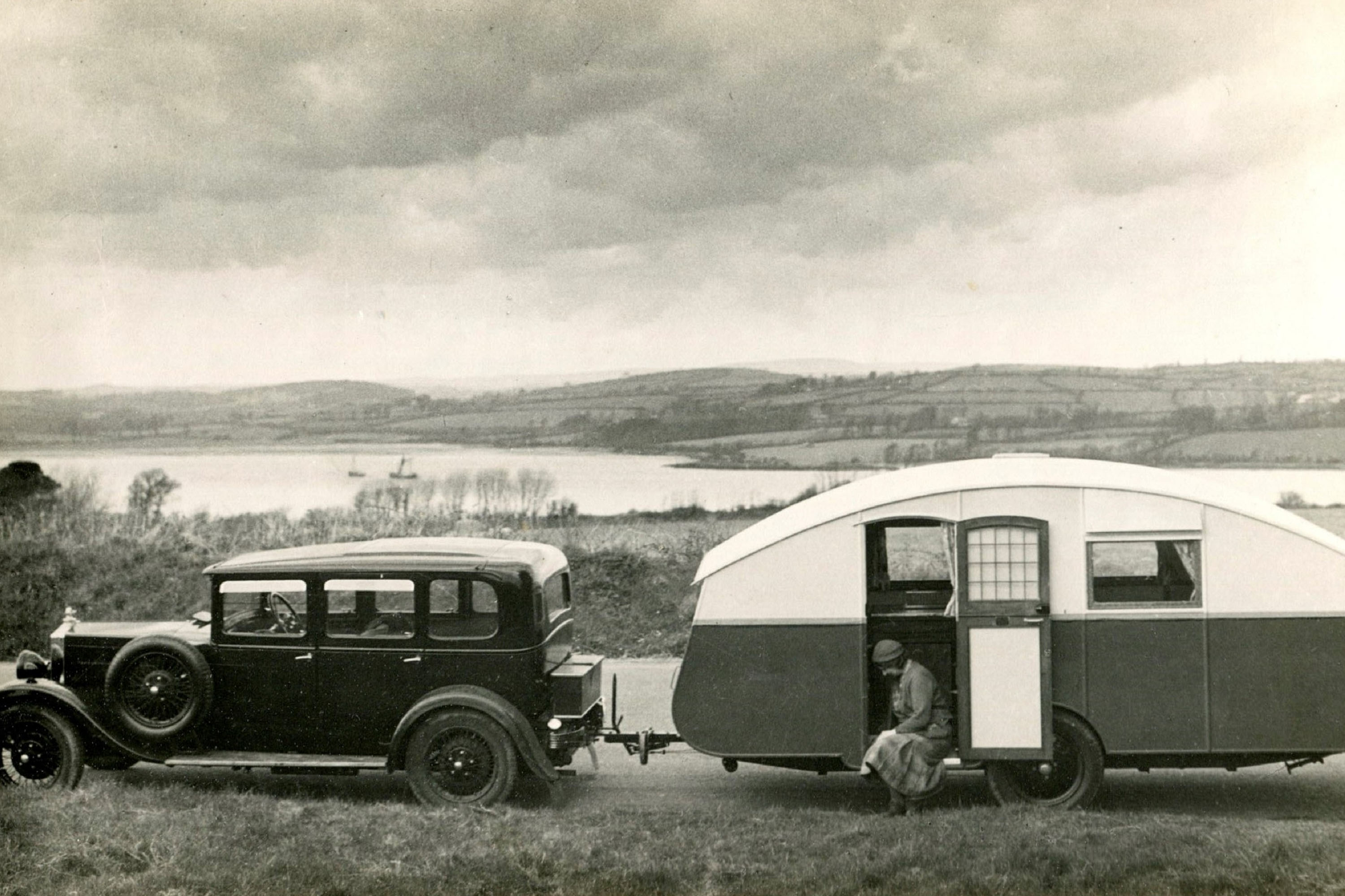 1930s car and caravan parked by a roadside with woman seated in doorway