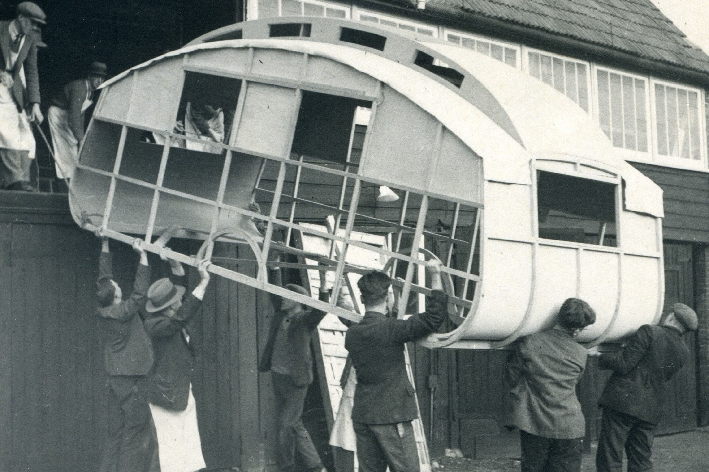 Workers lifting a caravan frame out of a workshop