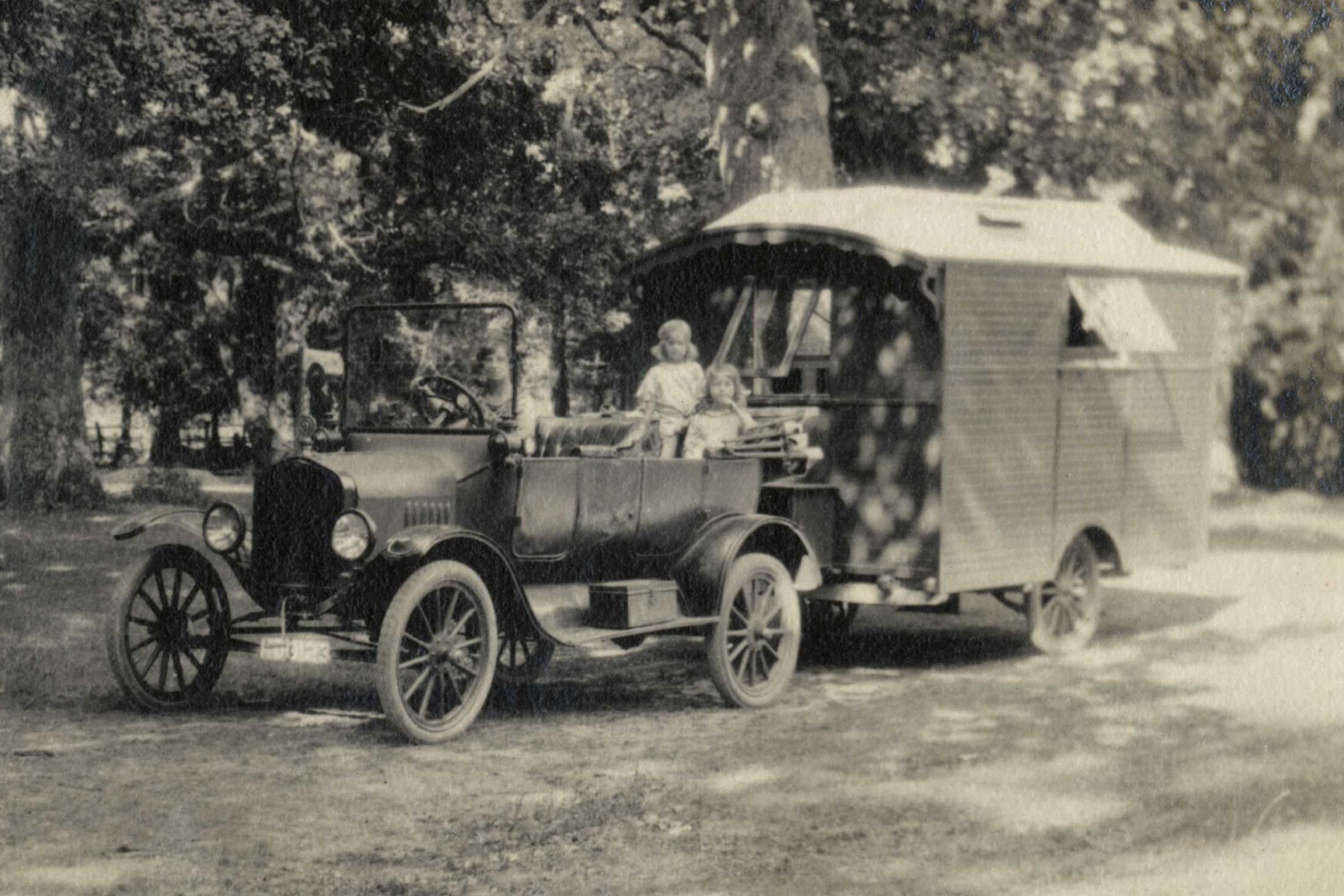A 1920s car and caravan in a Forest clearing with children seated in the car.