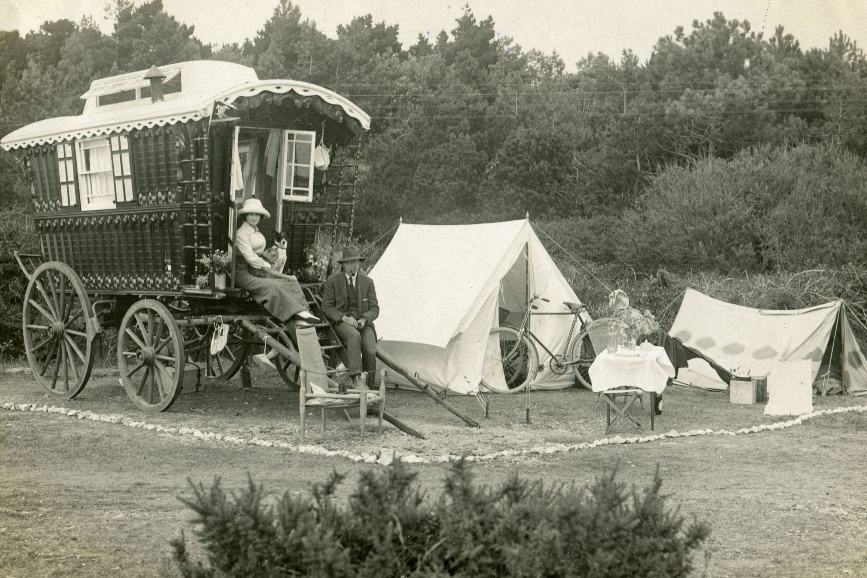 A camp comprising of a horse-drawn caravan and tents with man and woman