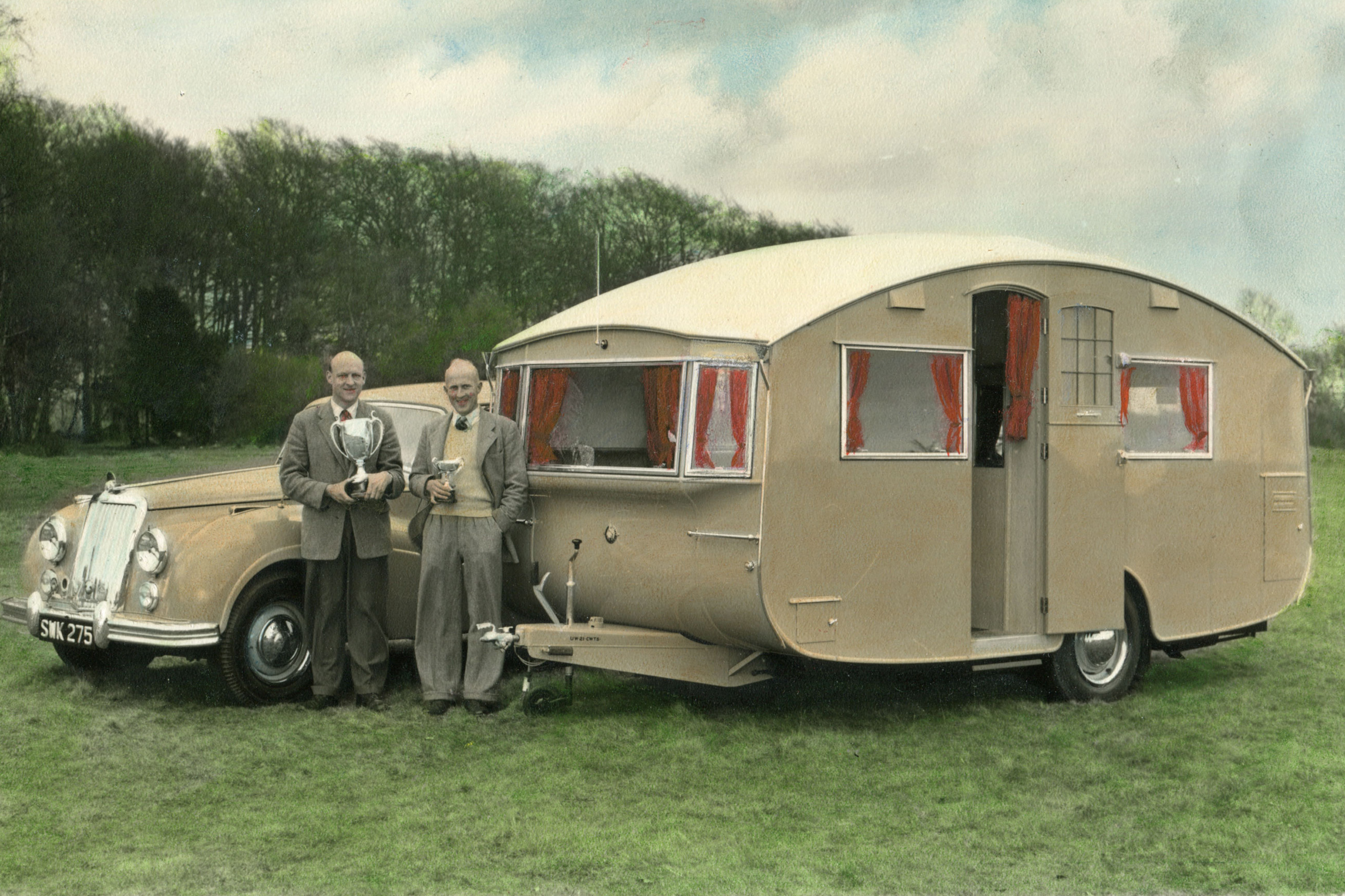 Two men holding trophies stood in front of a car and caravan