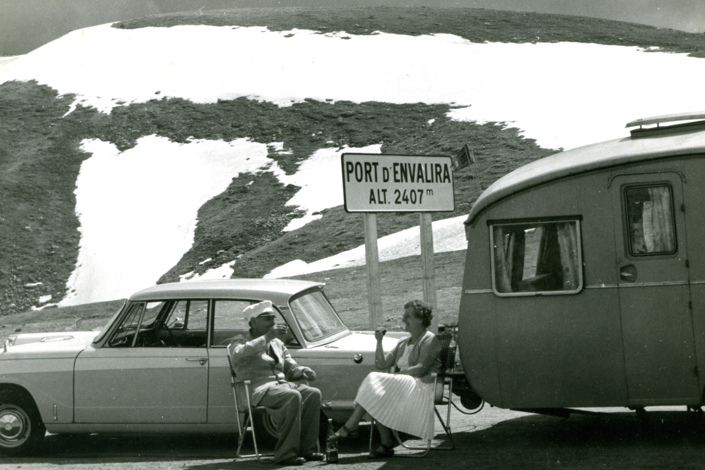Man and woman drinking tea next to their car and caravan with a view of mountains in the background