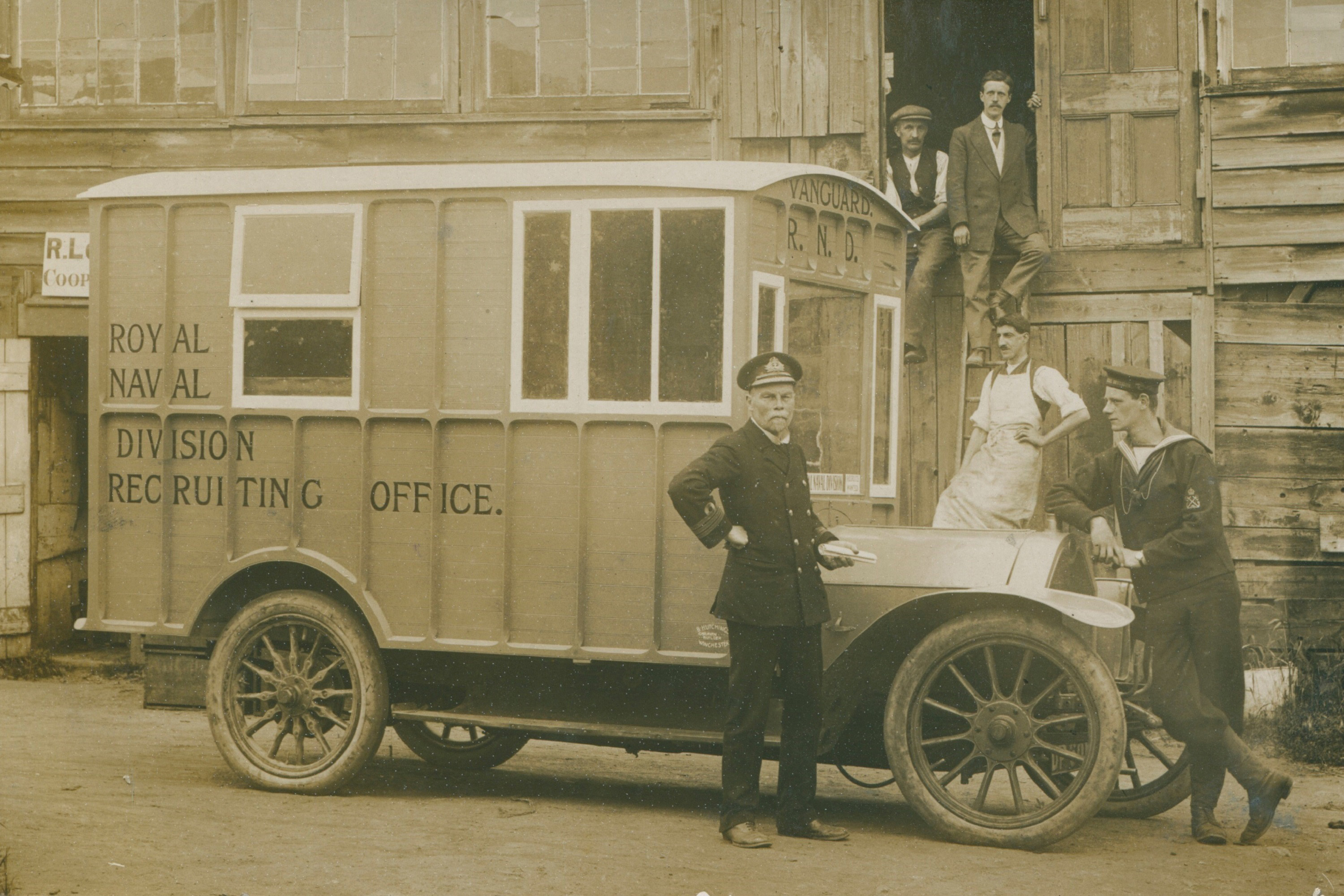 A man in uniform standing in front of a motor caravan with work men in the background