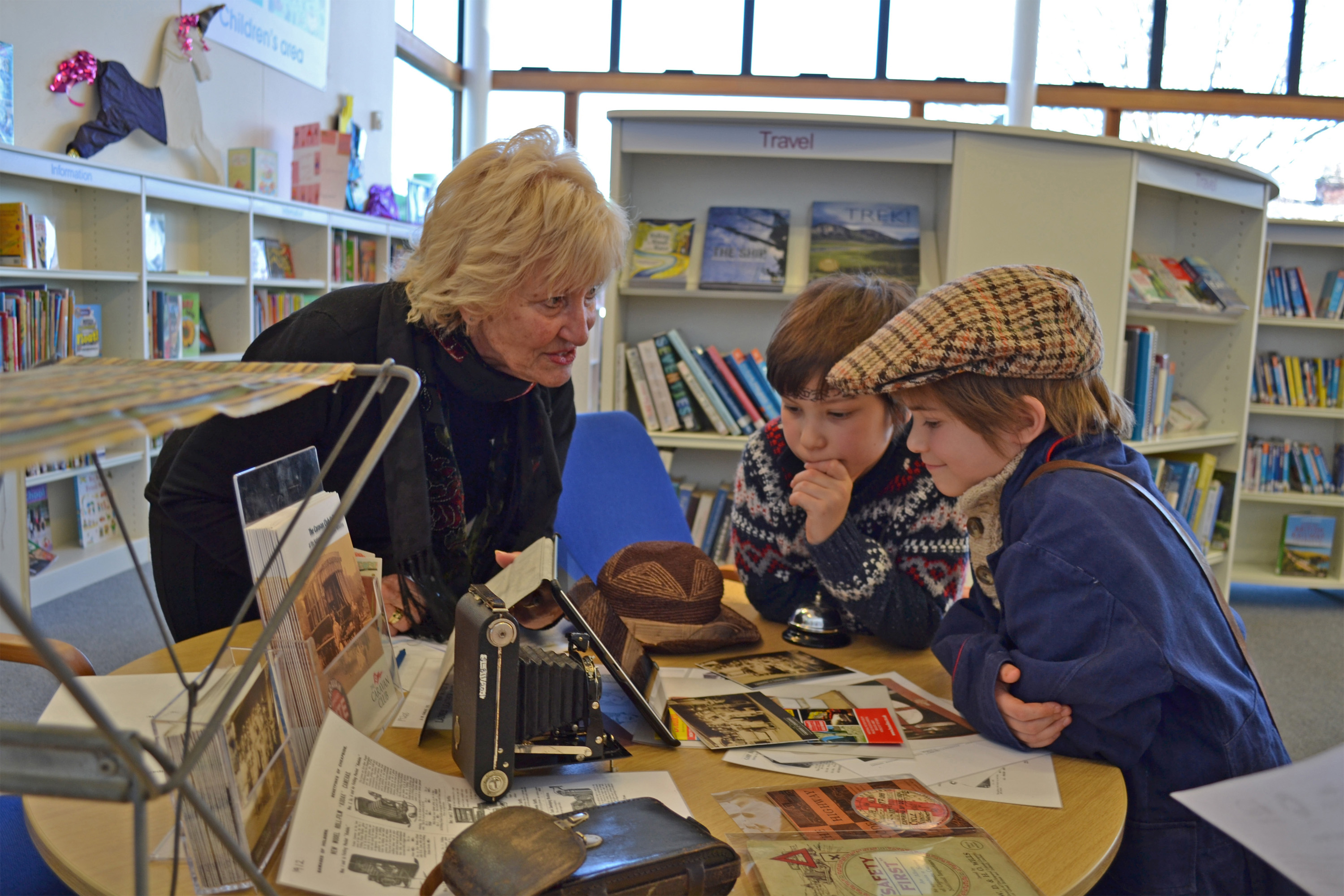Lady with two boys looking at historic items