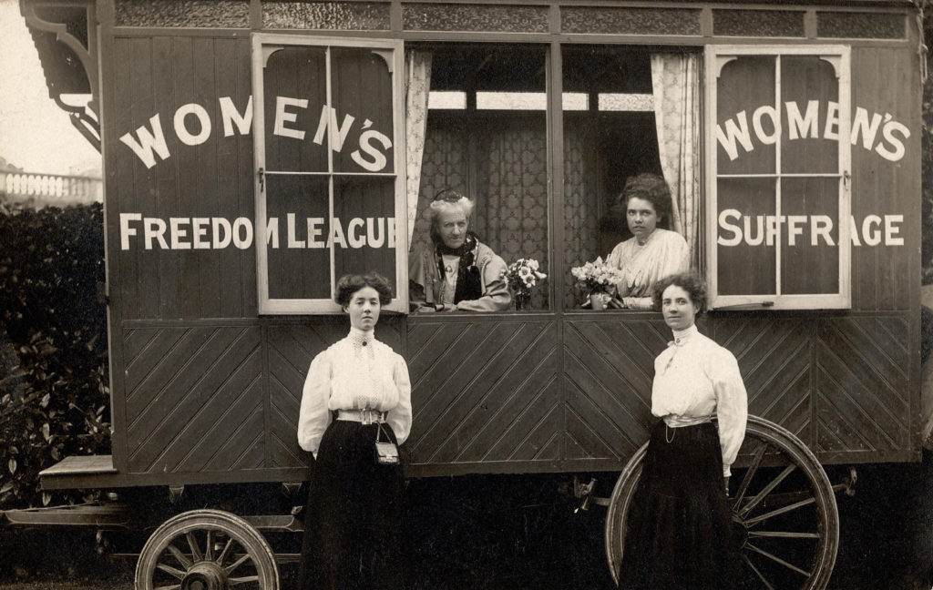 Women standing by a caravan painted with text reading Women's Freedom League