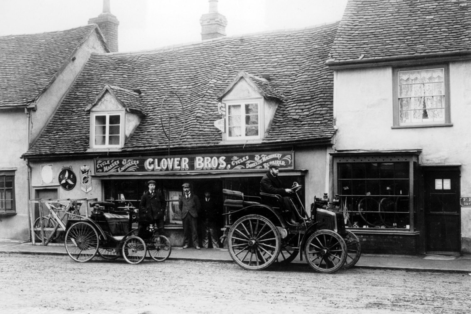 An archive image of a 1898 Benz and an early Panhard,, c1900, in a street outside Glover Bros cycle shop