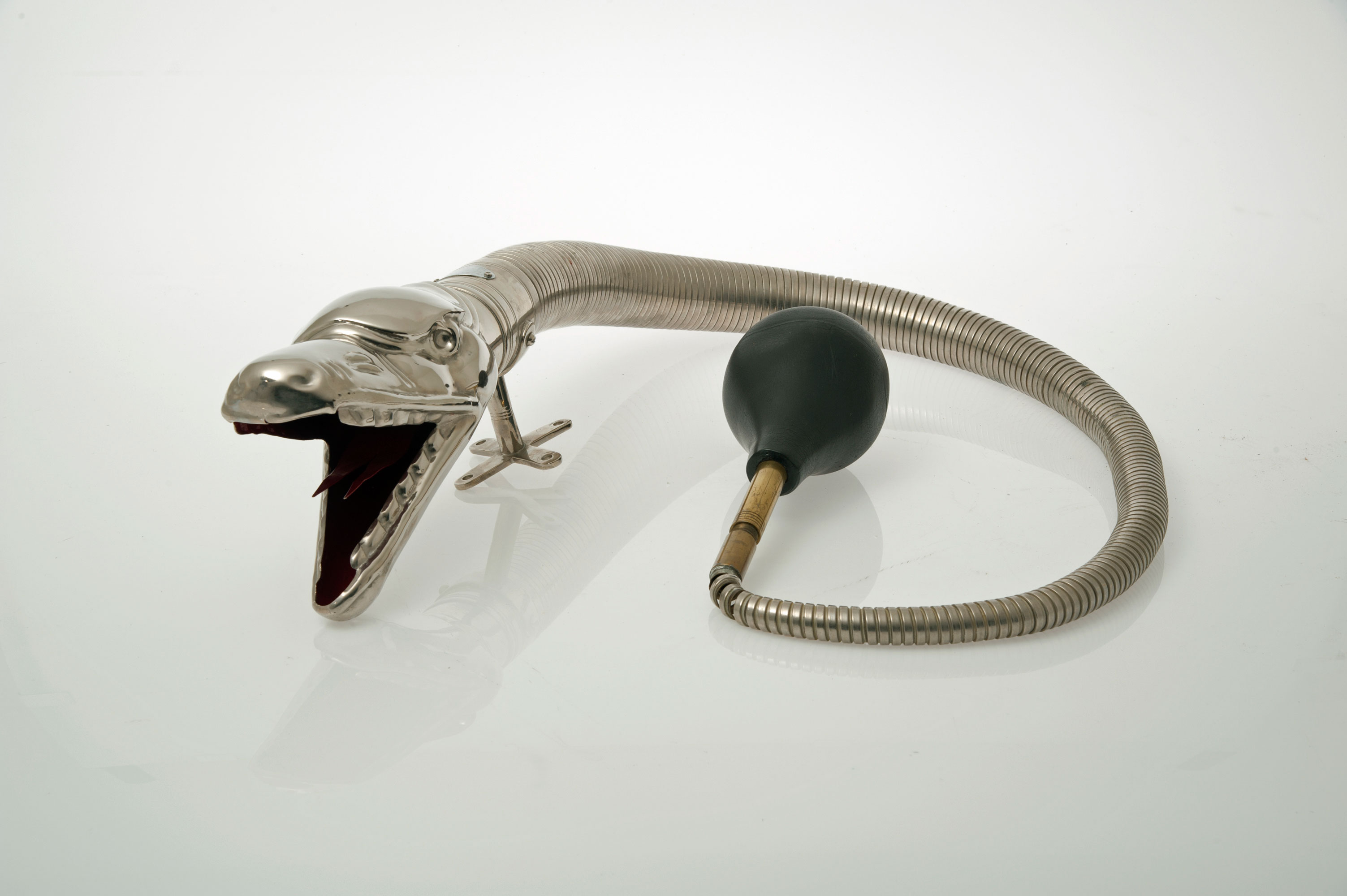 A historic silver car horn in the shape of a Boa snake