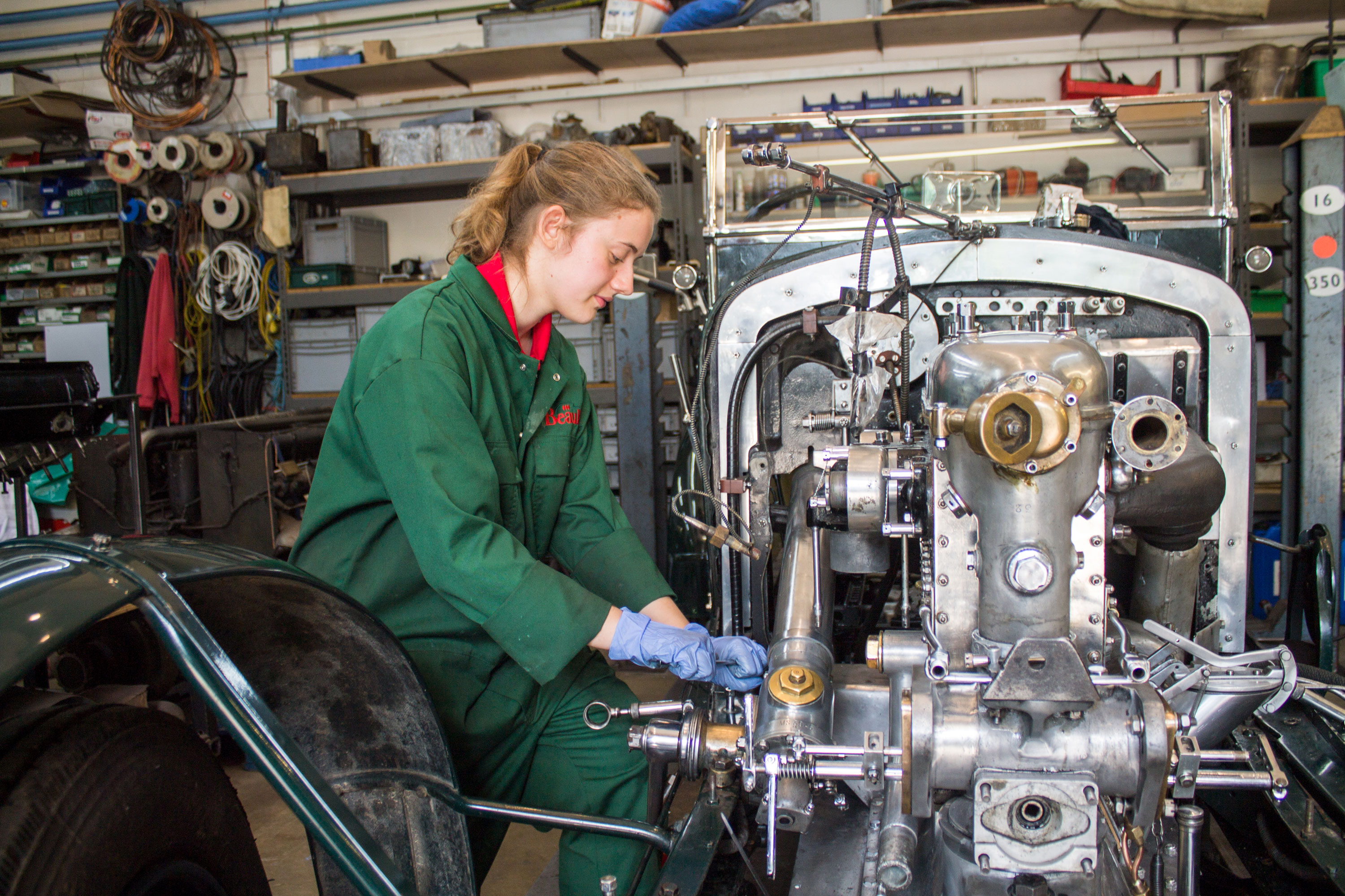 Workshop apprentice at the National Motor Museum working on a car engine