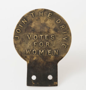 Metal Car Badge with Join the Drive Votes for Women text on it