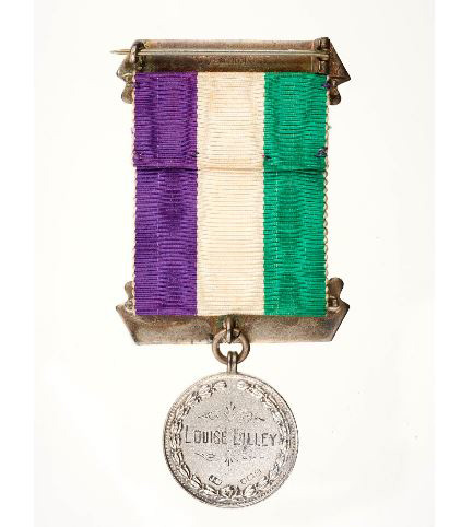 A medal in the suffrage colours of green, white and purple